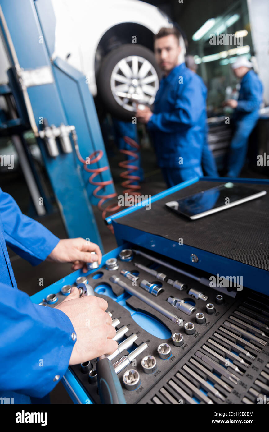 Professional car mechanic usin tools - Stock Image