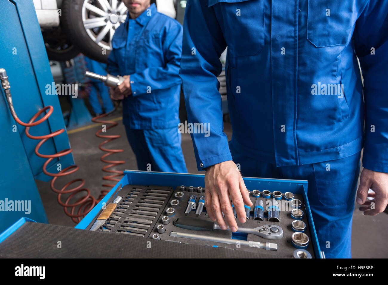 Professional car mechanic standing near set with tools - Stock Image