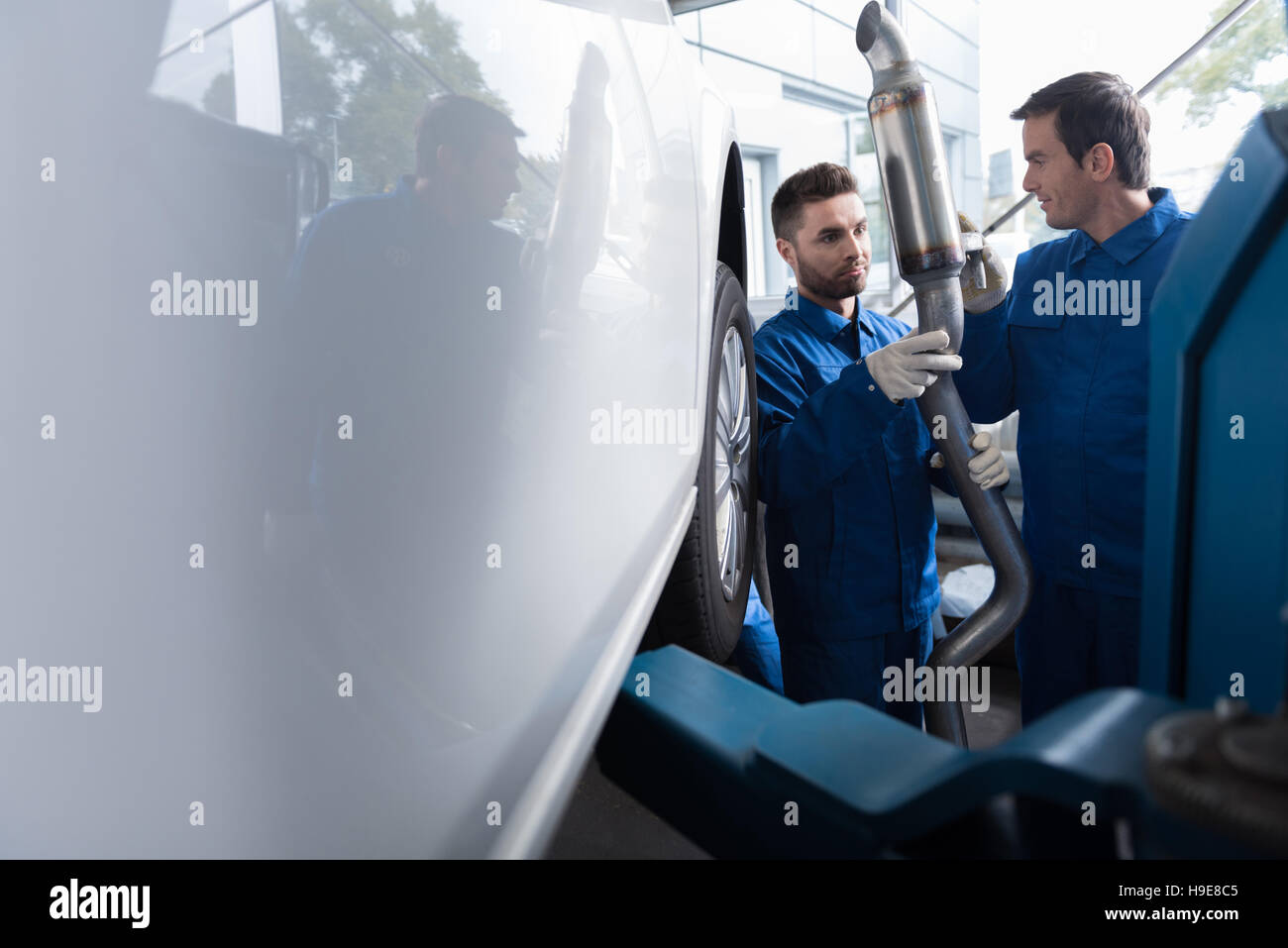 Professional car mechanics reparing muffler - Stock Image