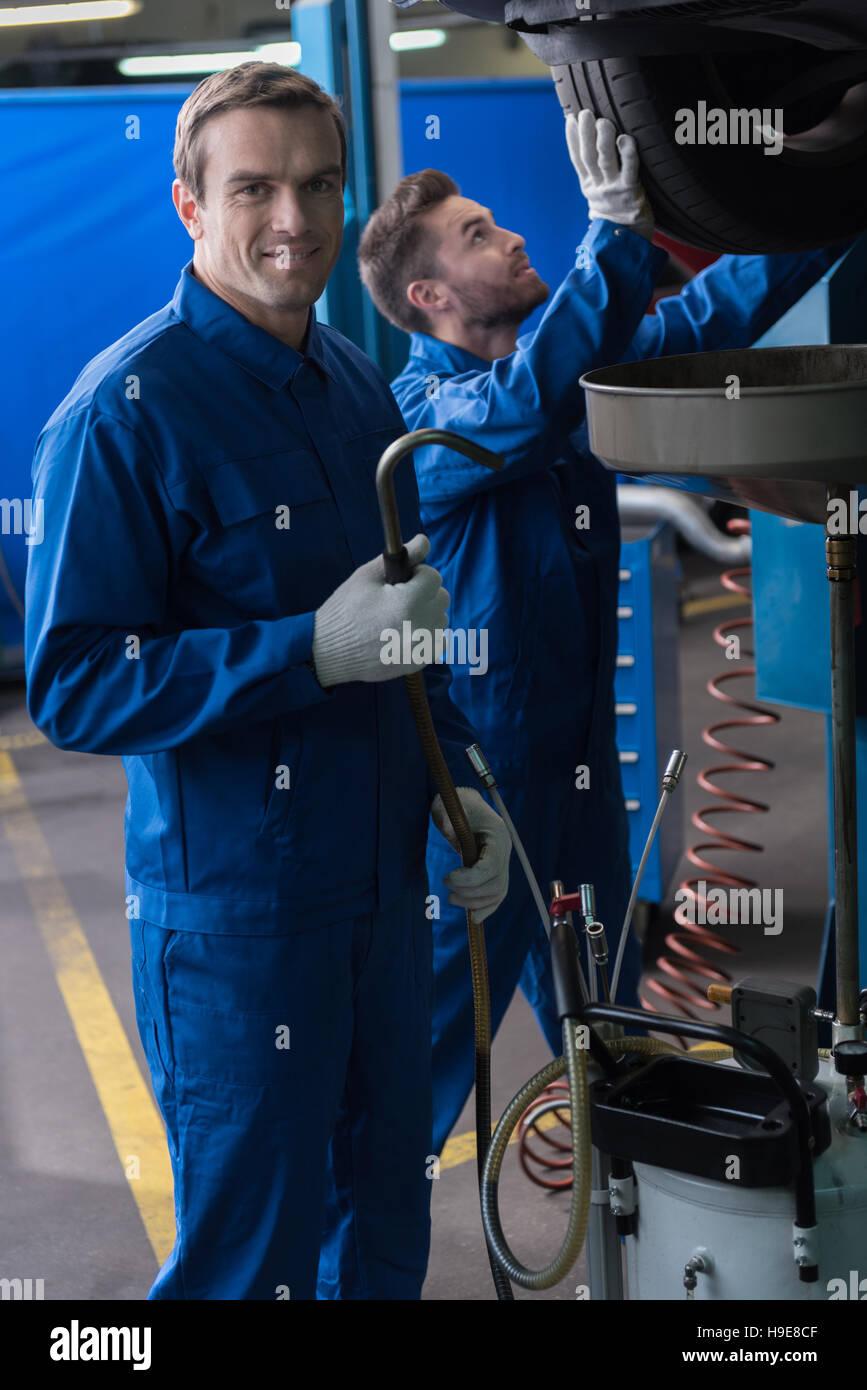 Positive mechanics working in auto service. - Stock Image