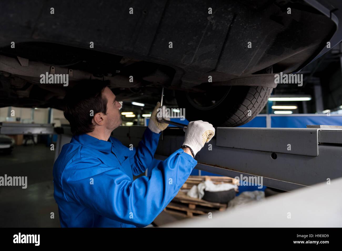 Professional mechanic reparing a car. - Stock Image