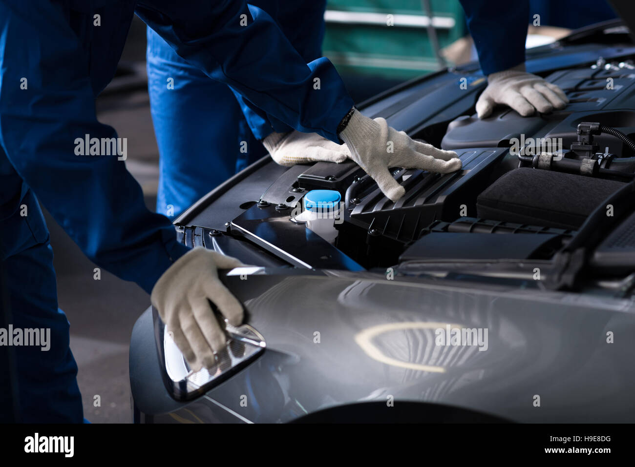 Professional mechanics chacking car engine - Stock Image