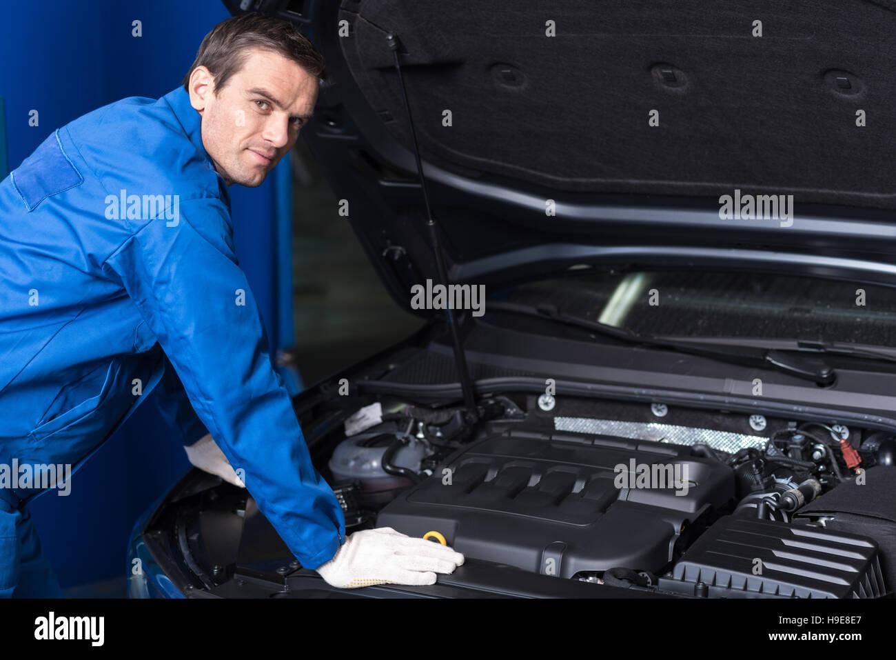 Professional confident mechanic chacking car engine - Stock Image