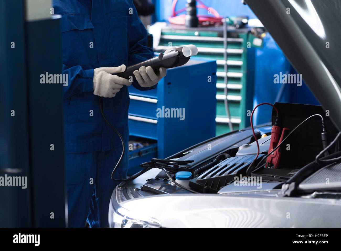 Professional mechanic checking car engine - Stock Image