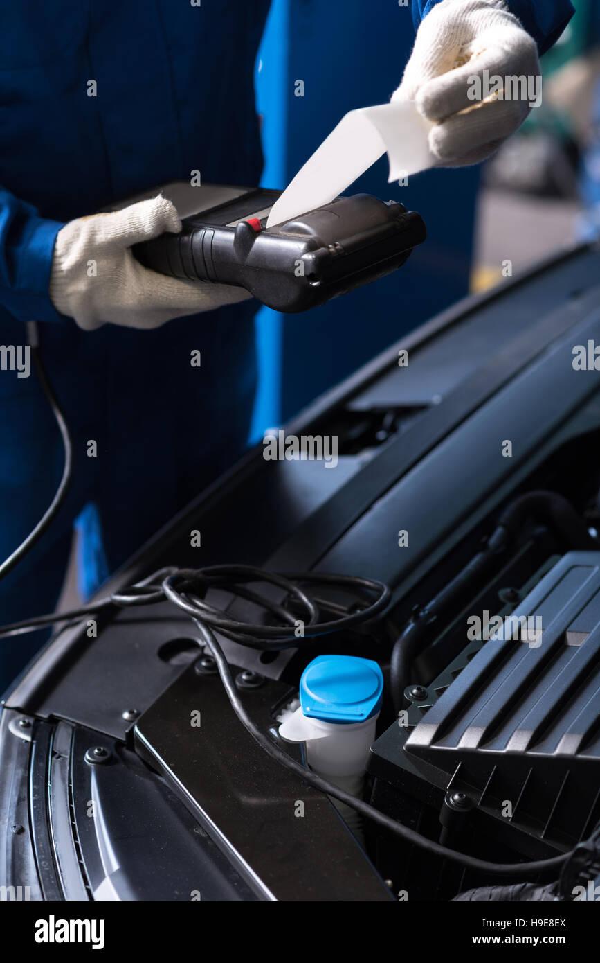 Professioanl auto mechanic checking engine - Stock Image