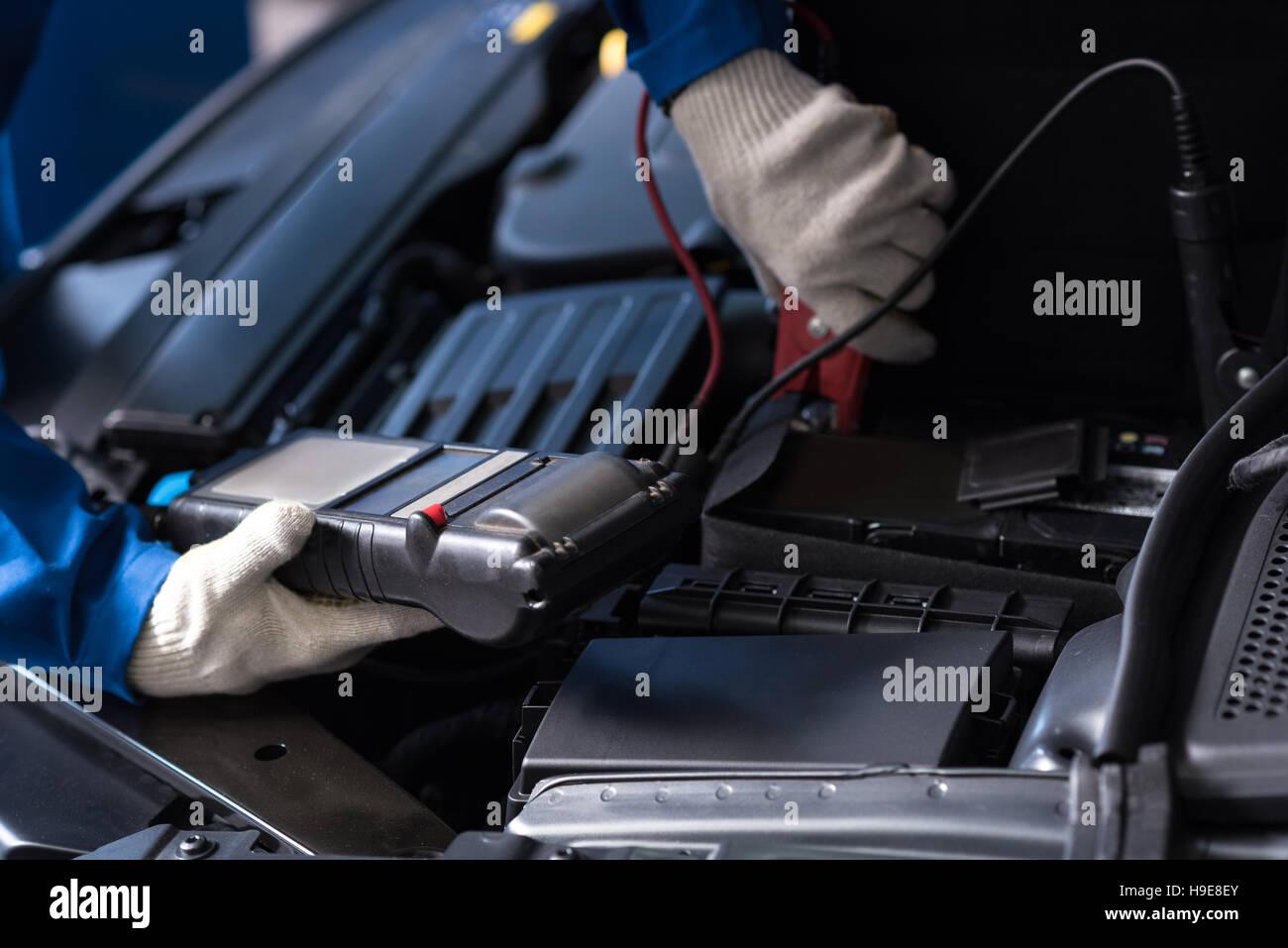 Professional mechanic examining car engine - Stock Image
