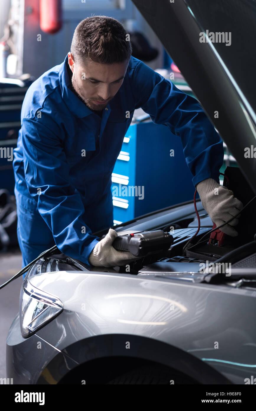 Professional mechanic examining engine - Stock Image