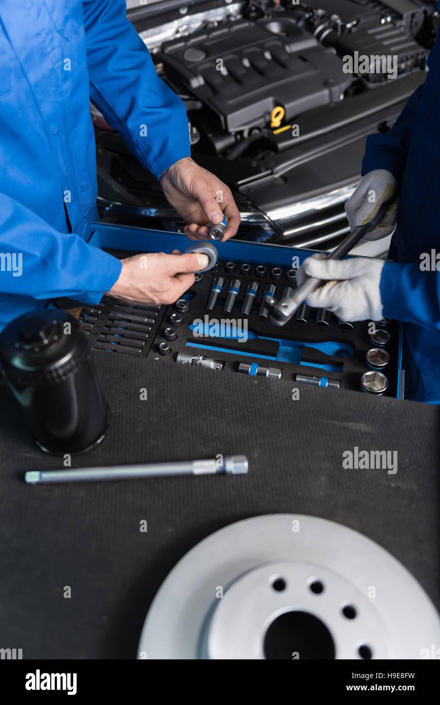 Professioanl mechanics putting tools in order - Stock Image
