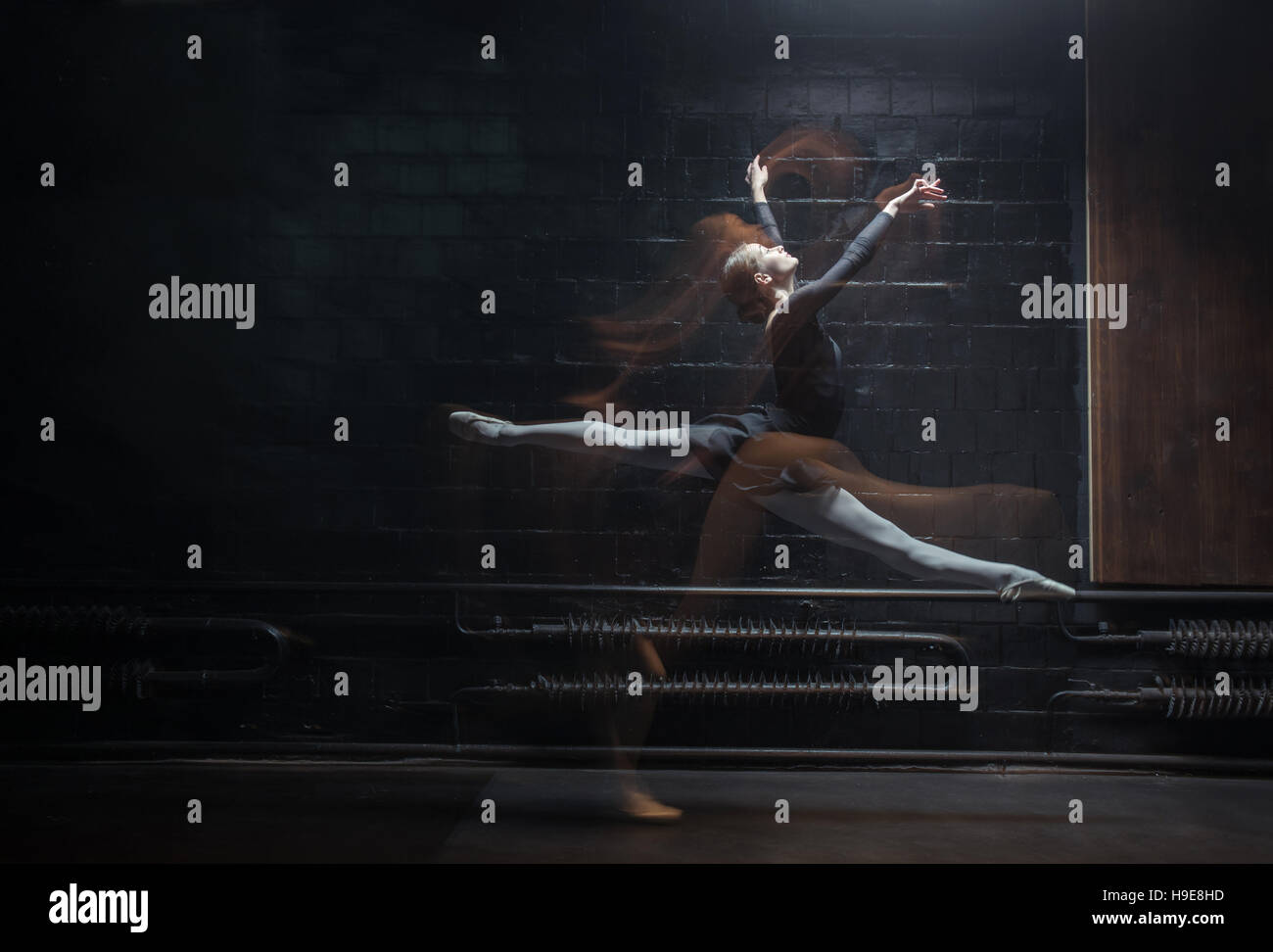 Young female gymnast showing her twine on the dark background - Stock Image