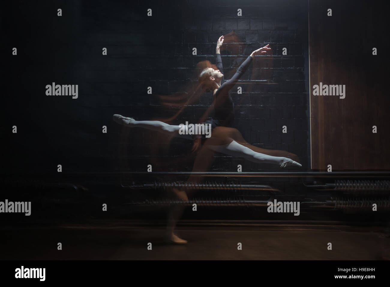 Delighted gymnast jumping on the dark background - Stock Image
