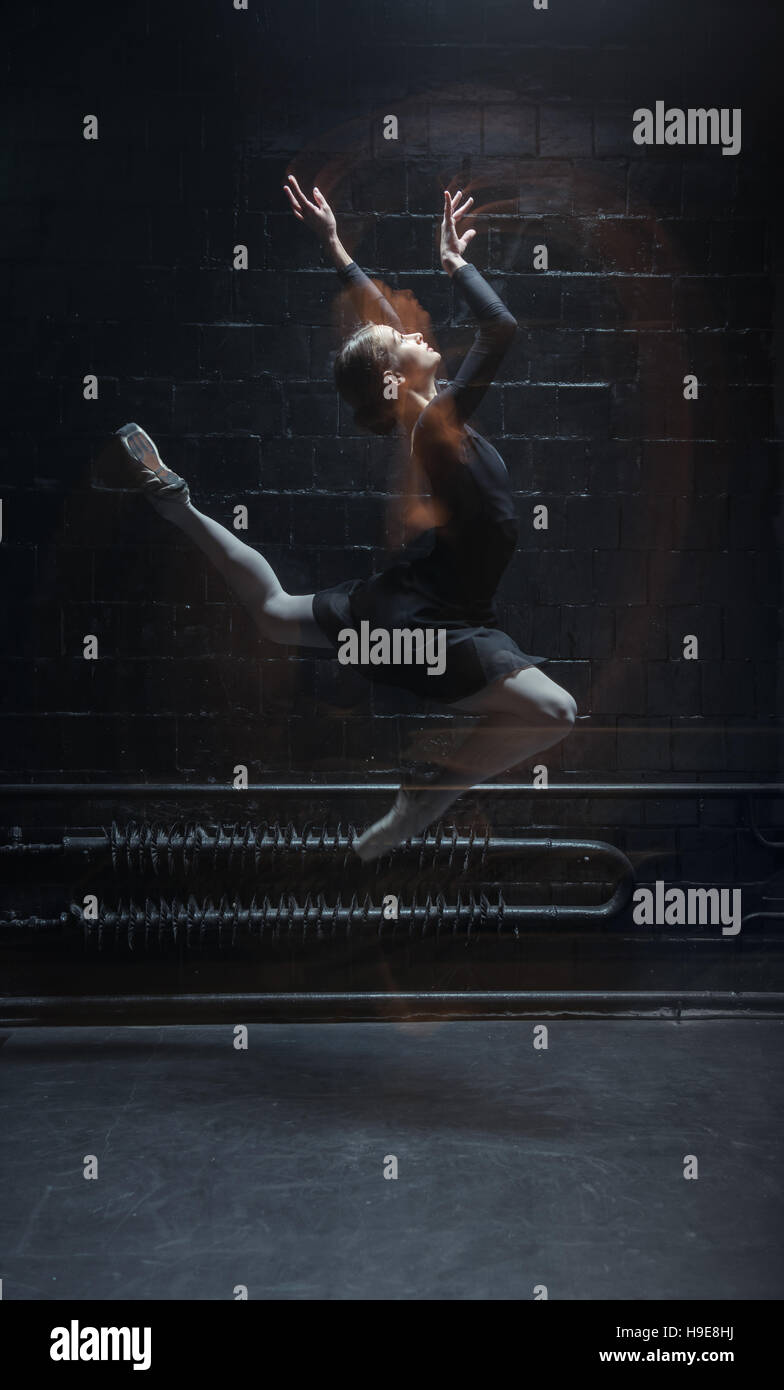 Inspired dancer jumping on the dark background - Stock Image