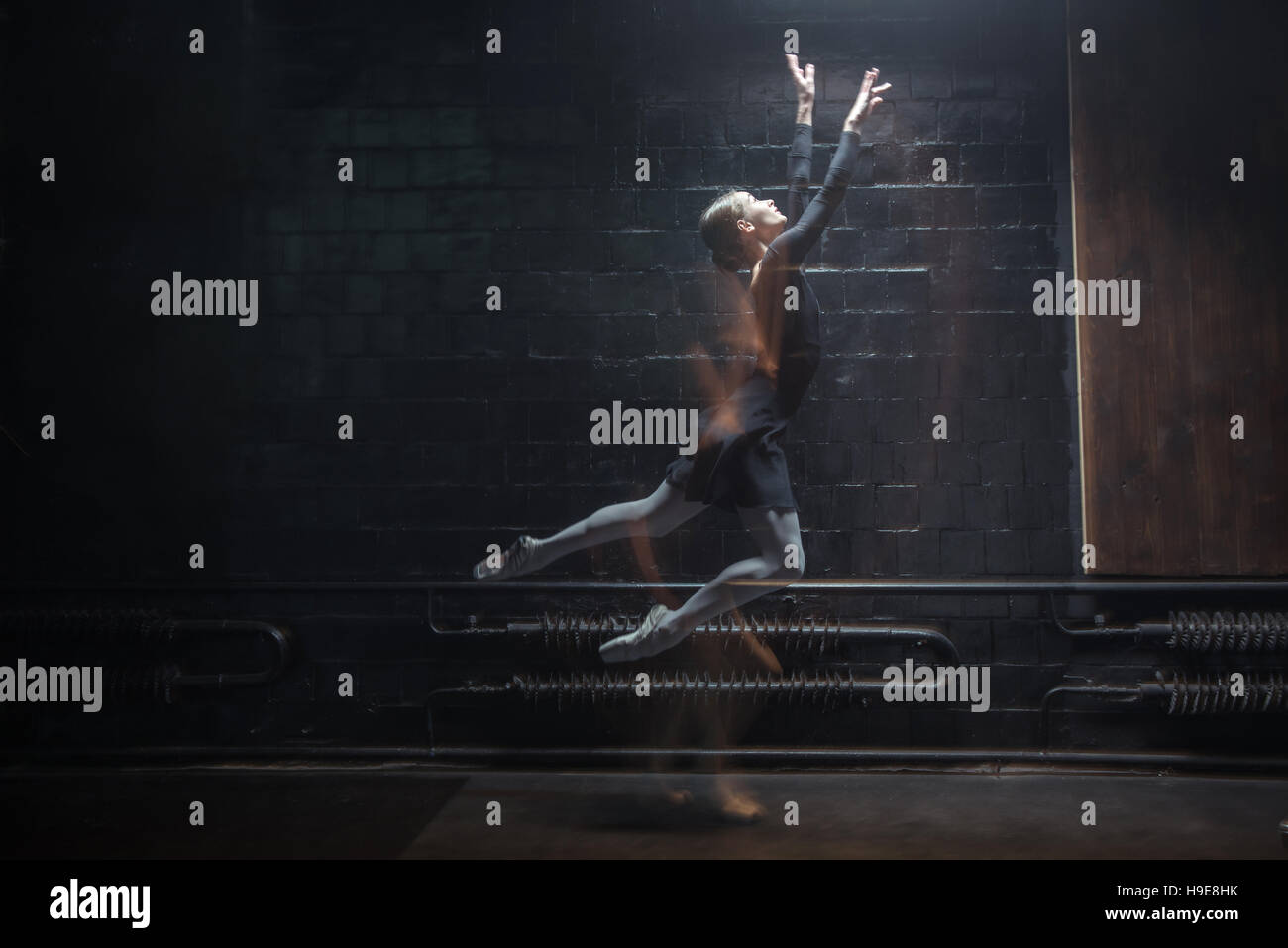 Inspired ballet dancer jumping on the dark background - Stock Image