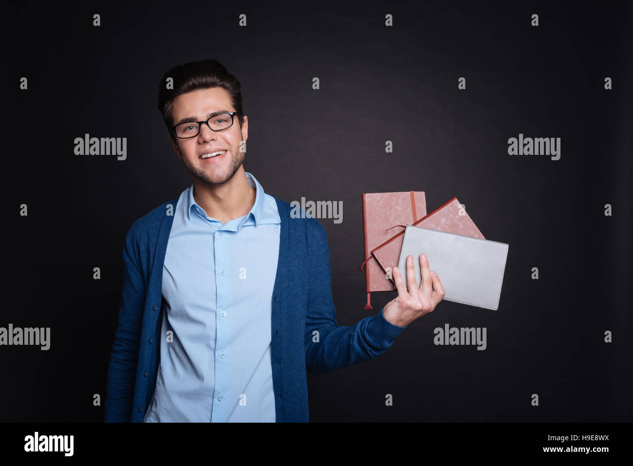 Pleasant smiling man holding diaries. - Stock Image