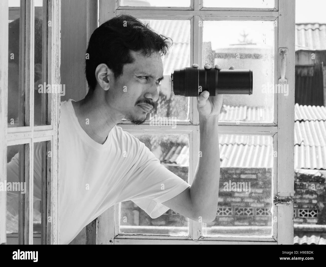 Man looking out through a window using a telephoto lens. Humorous concept in Black and white photography. - Stock Image