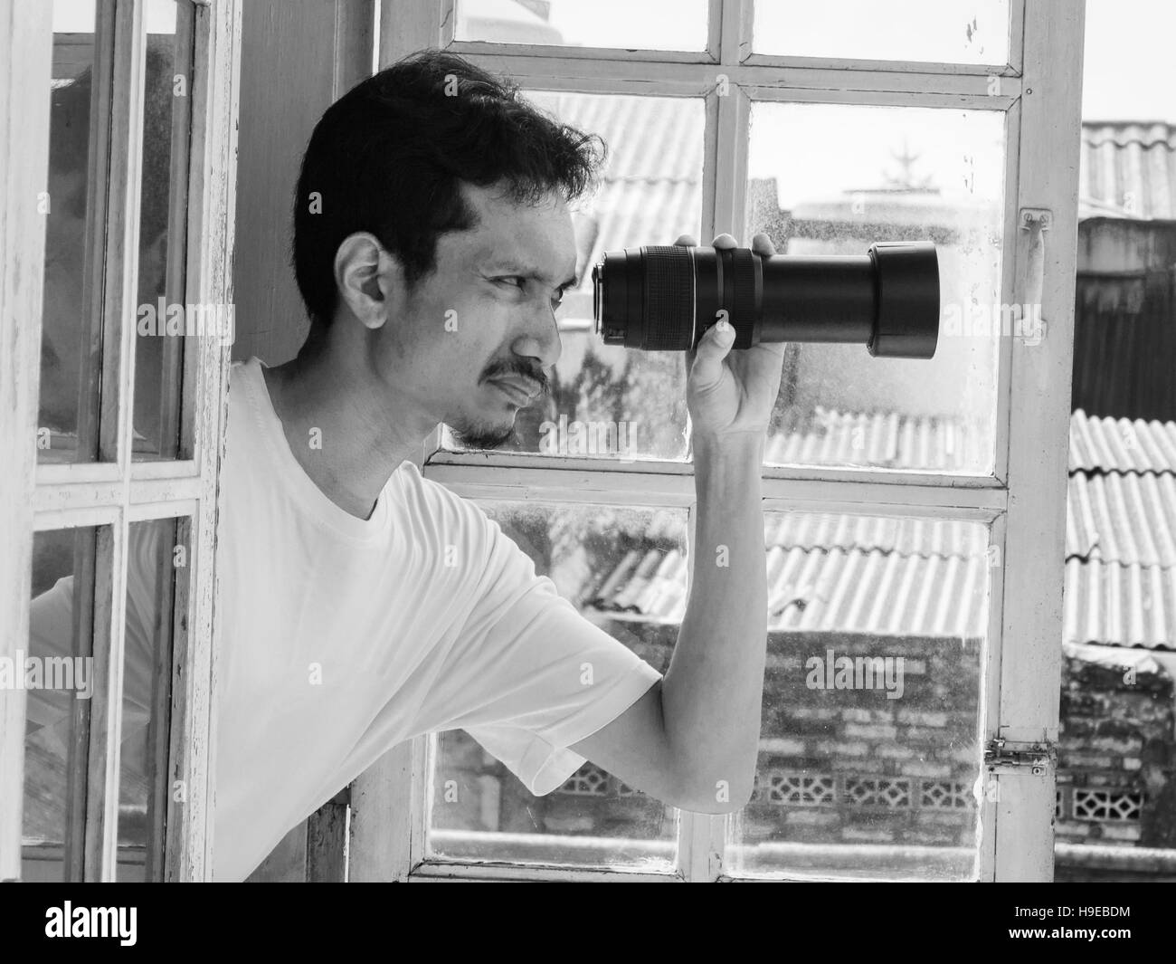 Man looking out through a window using a telephoto lens. Humorous concept in Black and white photography. Stock Photo
