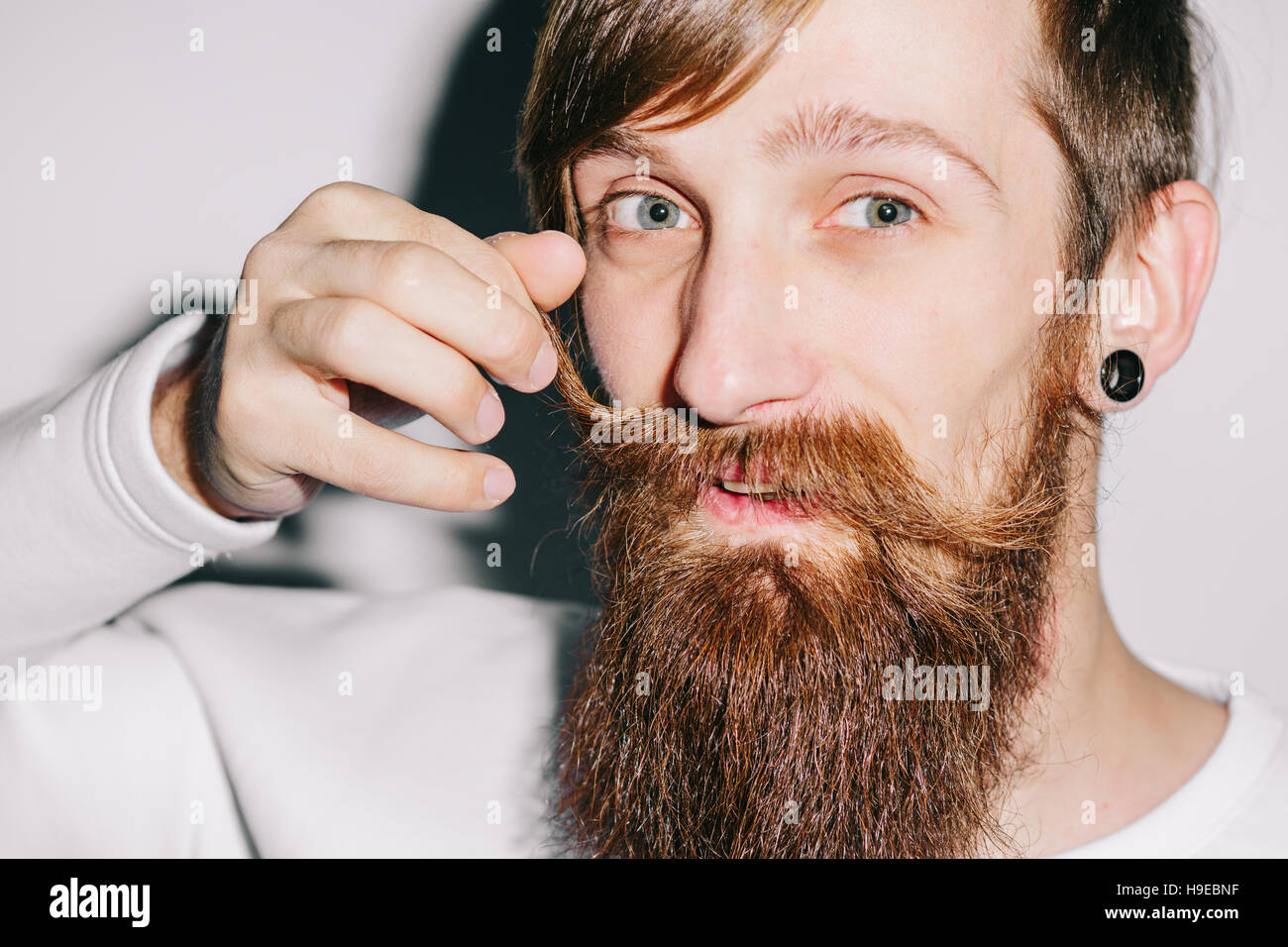 Bearded man twirling his mustache - Stock Image
