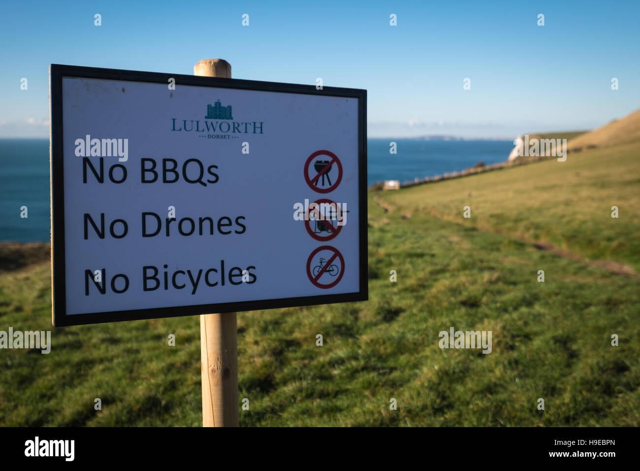 A sign for visitors to Durdle Door 'No BBQs, No Drones & No Bicycles'. - Stock Image