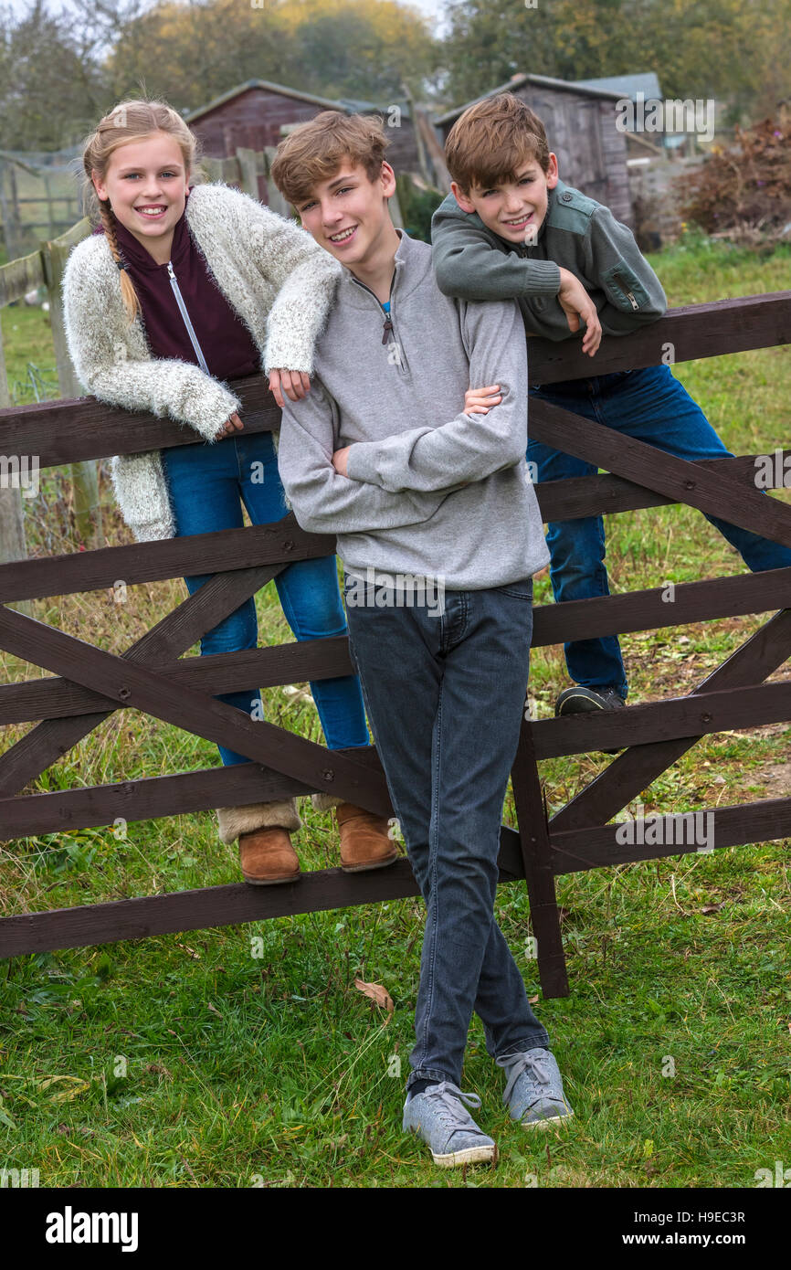 Three children two boys and girl, family brothers and sisters, leaning on a gate in a country garden - Stock Image