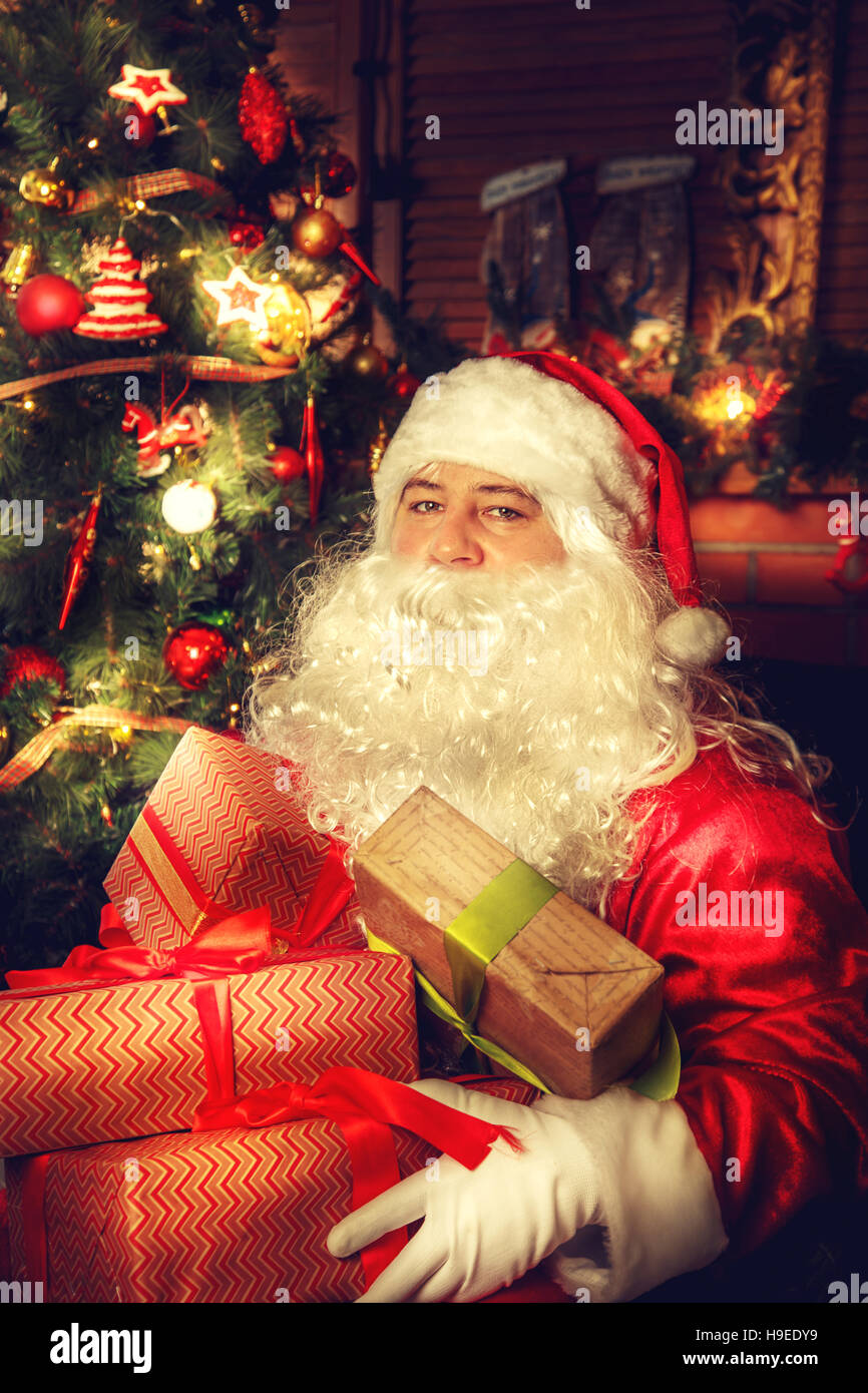 Real Santa Claus. Santa Claus Sitting In The Living Room Near The Christmas  Tree With Gifts.