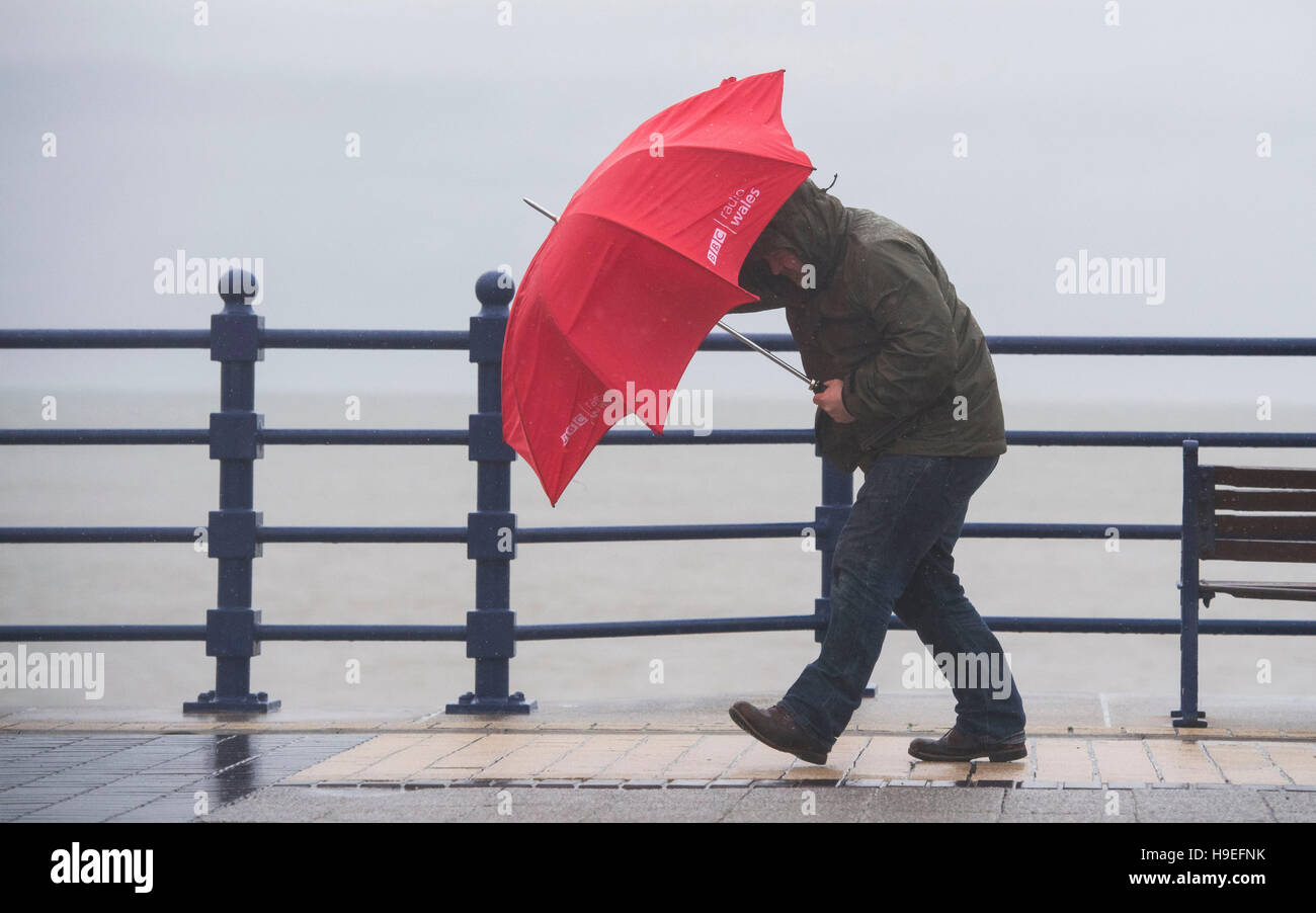 A man battles strong winds with a red umbrella during storm Angus in Porthcawl, South Wales, UK. - Stock Image