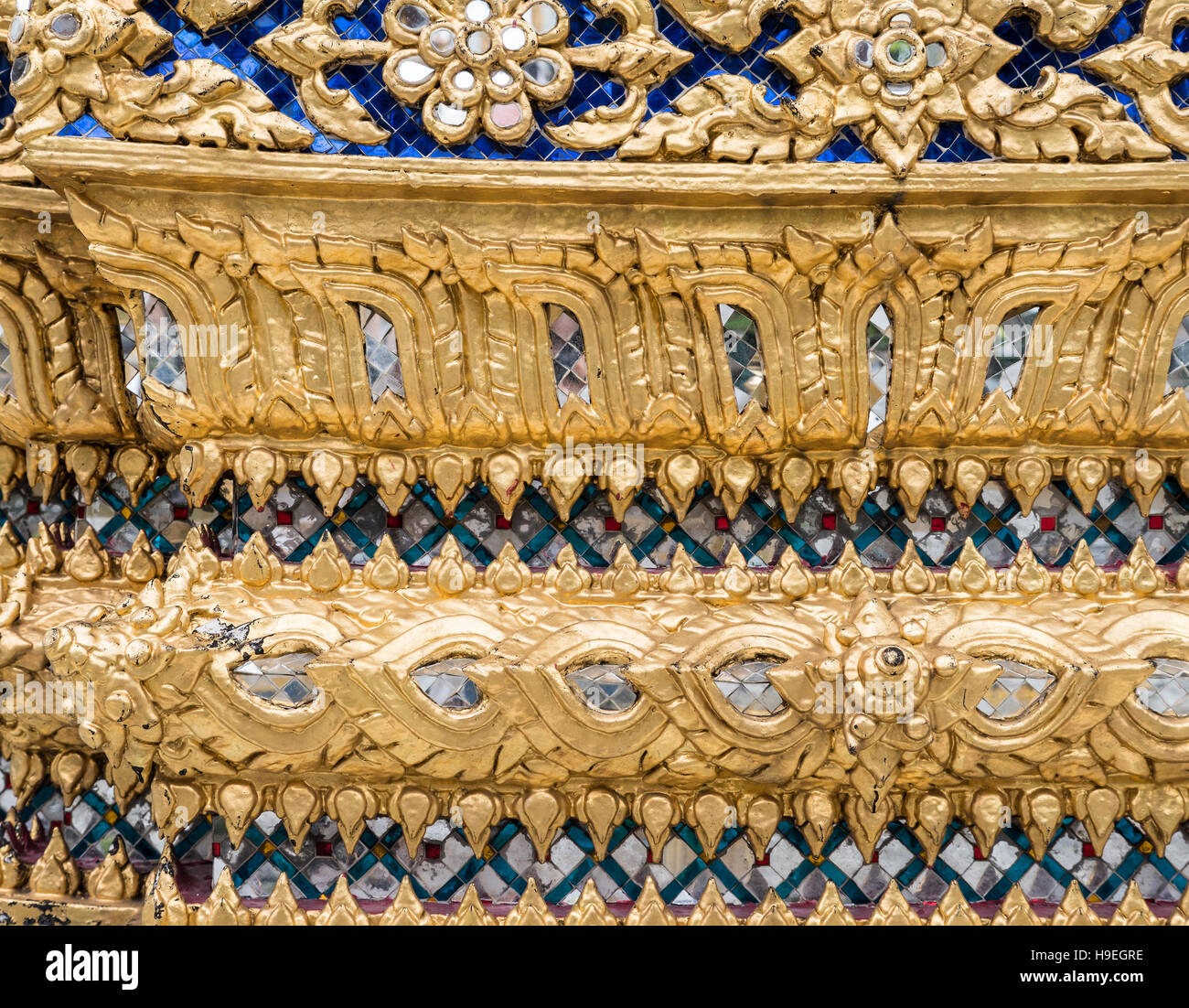 Golden flower pattern with glass mosaic on the church wall in the Thai temple. (Public area not required Property - Stock Image