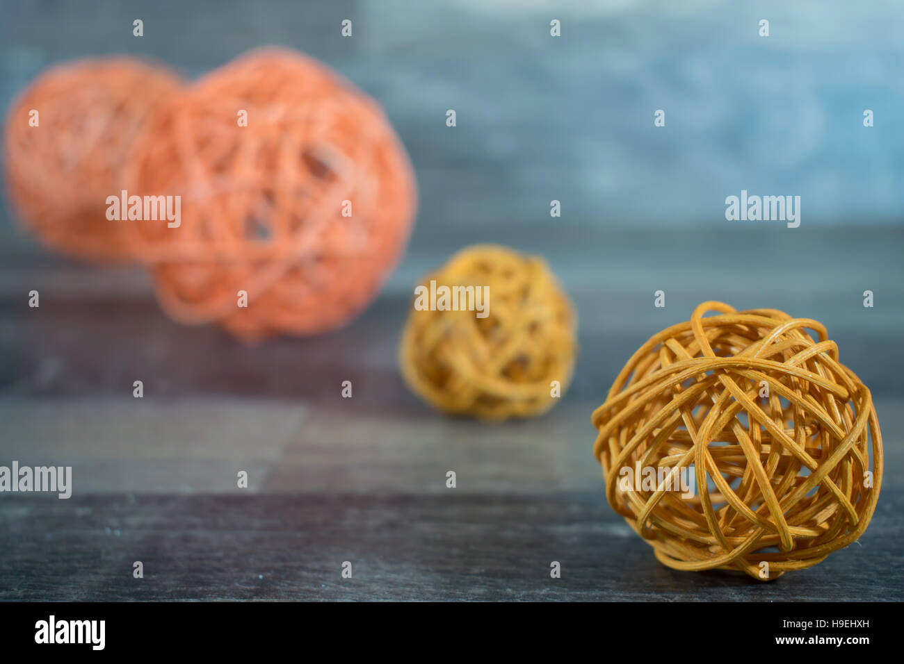 4 braided balls in yellow and orange on a wooden base - Stock Image