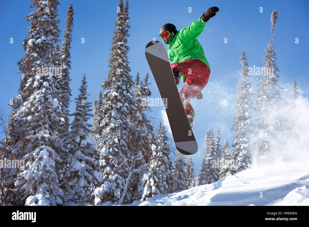 Snowboarder jumps freeride powder forest - Stock Image