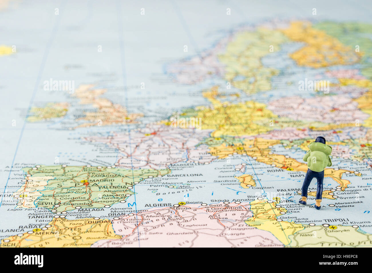 closeup of miniature figurine of young traveller standing on big map next to Europe continent - Stock Image