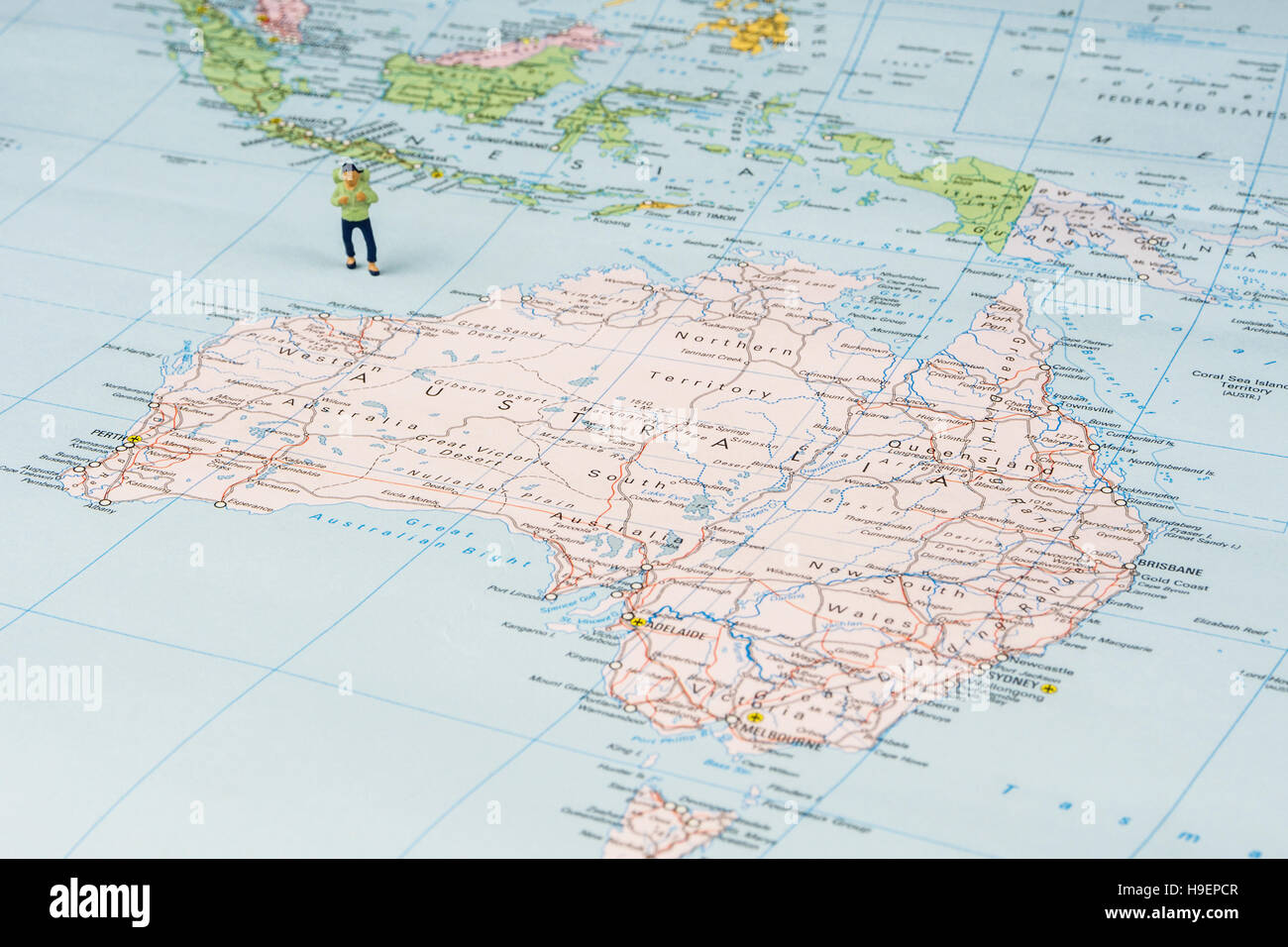 Young Australia Map.Closeup Of Miniature Figurine Of Young Traveller Standing On Big Map