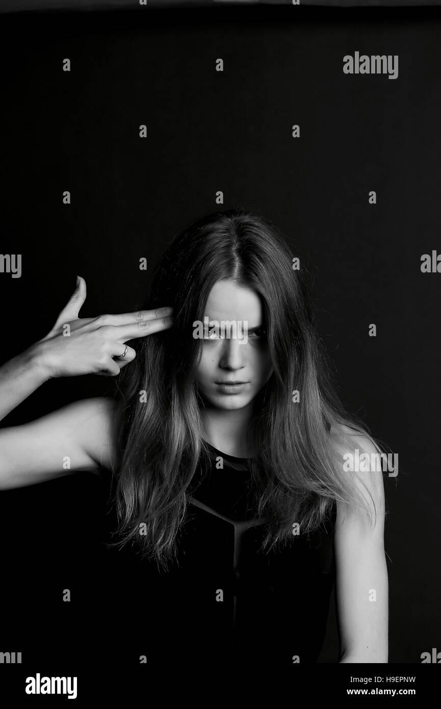 Beautiful girl. The gesture of fingers the gun - Stock Image