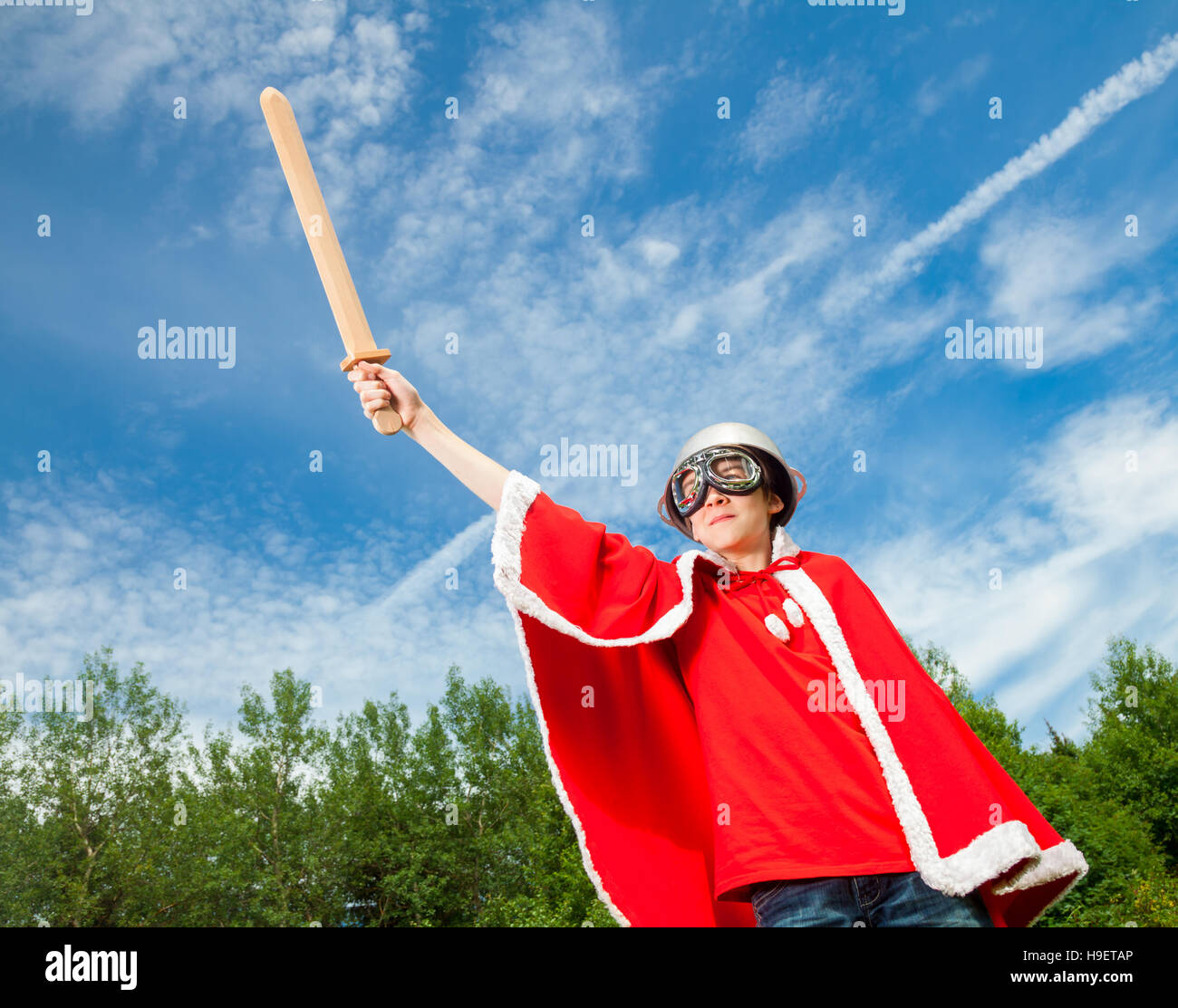 Low angle view of cute teenage boy wearing metal colander as a helmet goggles and red costume holding wooden sword - Stock Image
