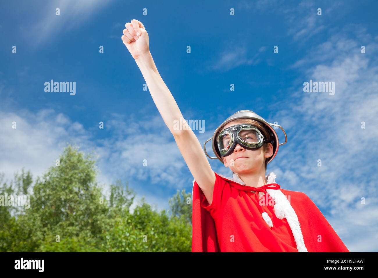 Low angle view of cute teenage boy wearing metal colander as a helmet goggles and red costume pretending to be a - Stock Image
