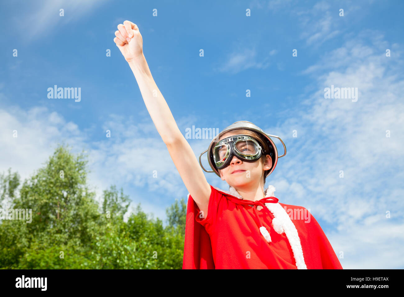 Low angle view of cute teen boy wearing metal colander as a helmet goggles and red costume - a funny power super - Stock Image
