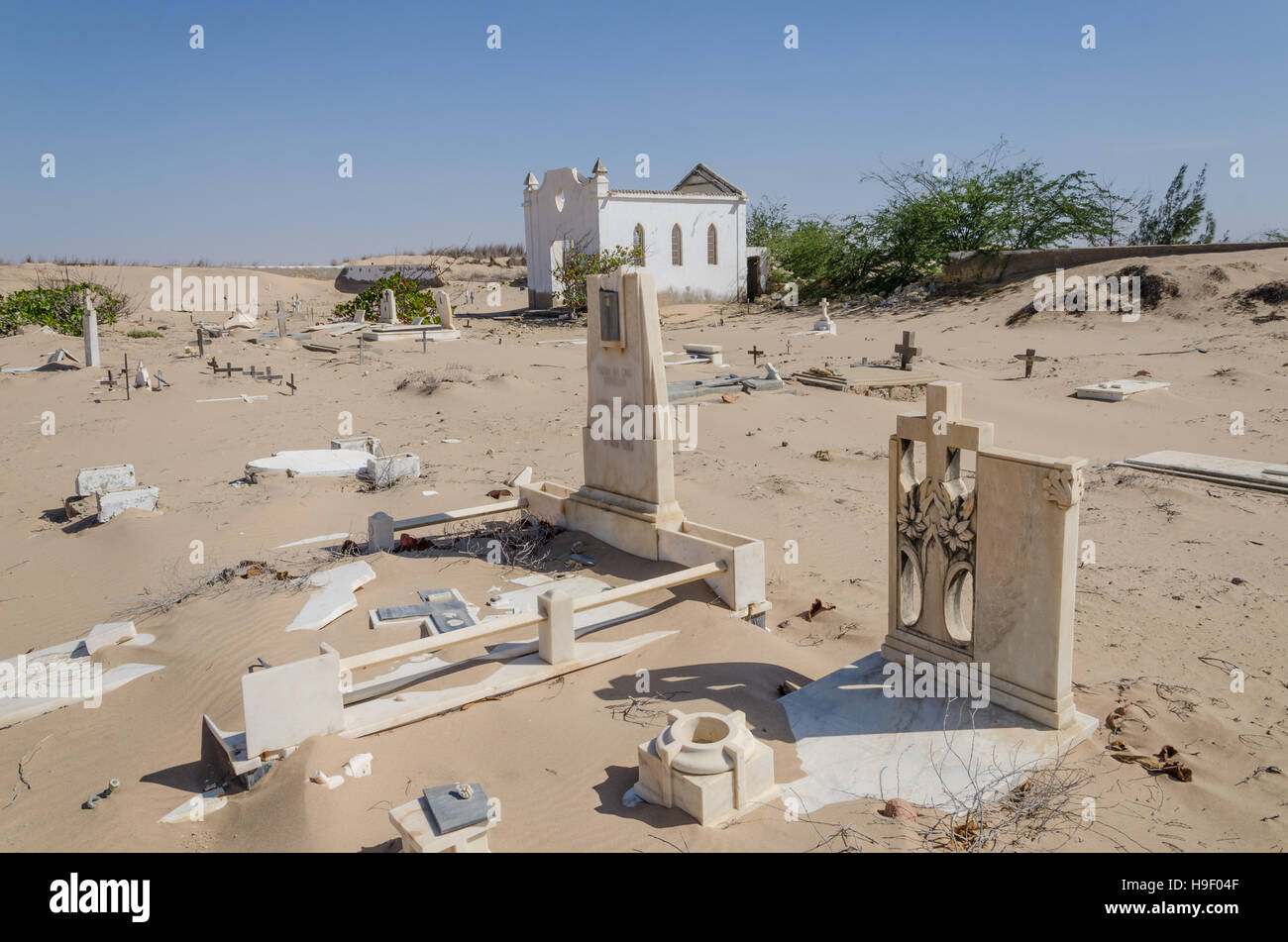 Abandoned graveyard with crumbling stones and crosses in Namib Desert of Angola - Stock Image