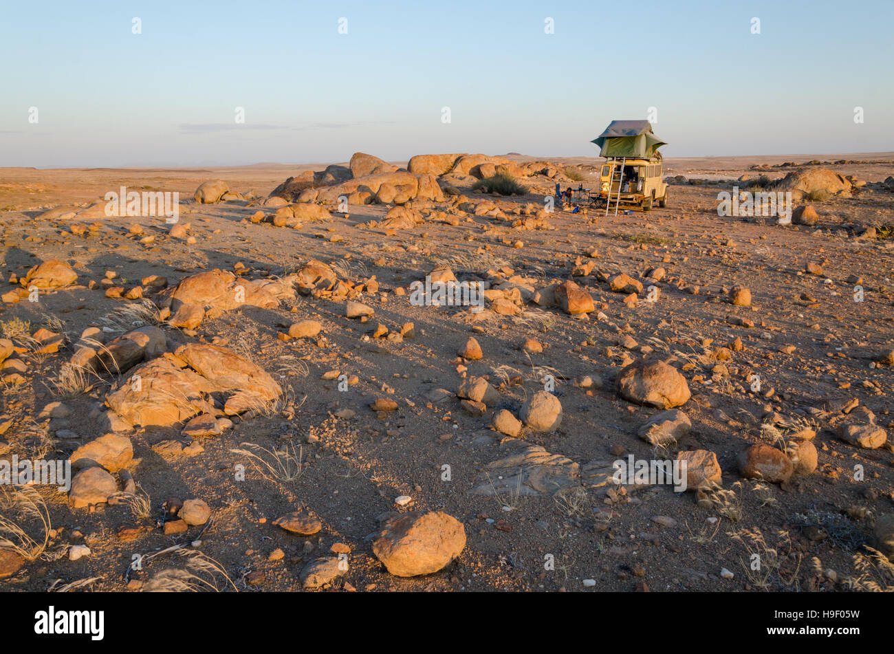 Camping with a 4x4 and roof top tent in a rocky part of Angola's Namib Desert. - Stock Image