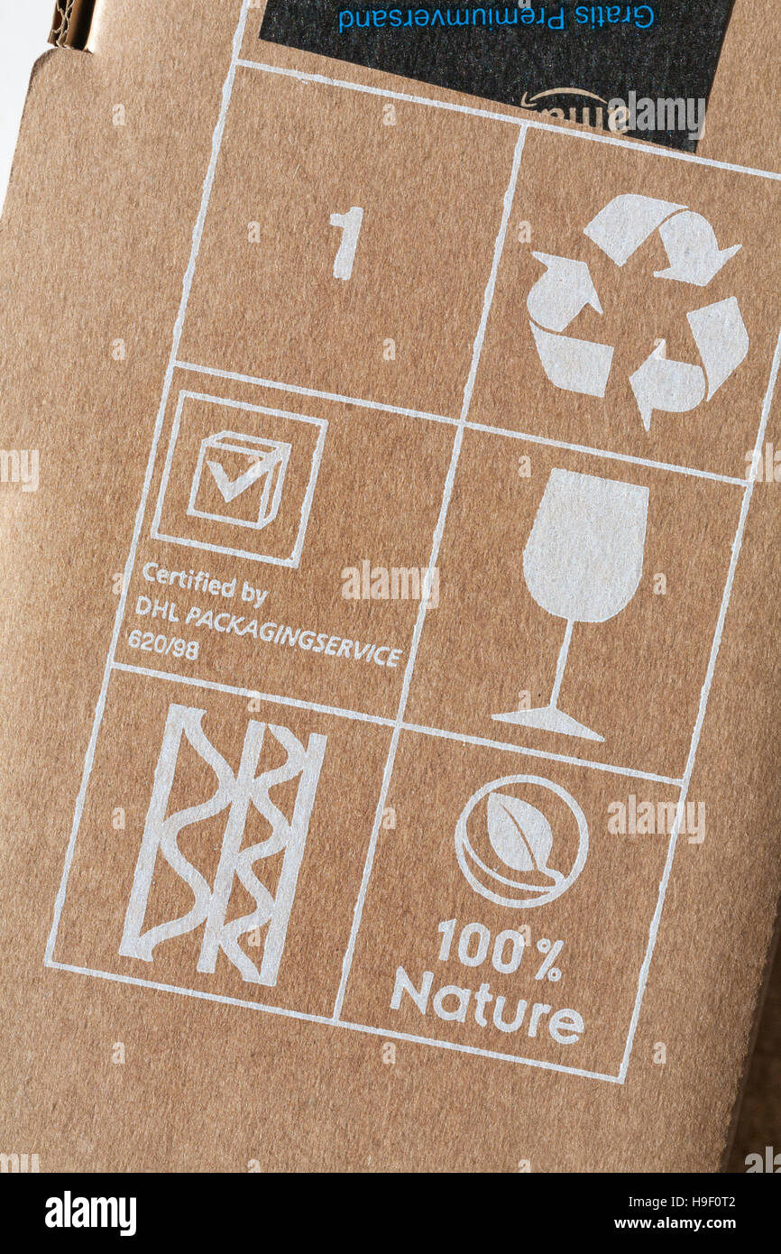 symbols on parcel from Amazon - glass, 100% nature, recyclable, corrugated, certified by DHL packaging service - Stock Image