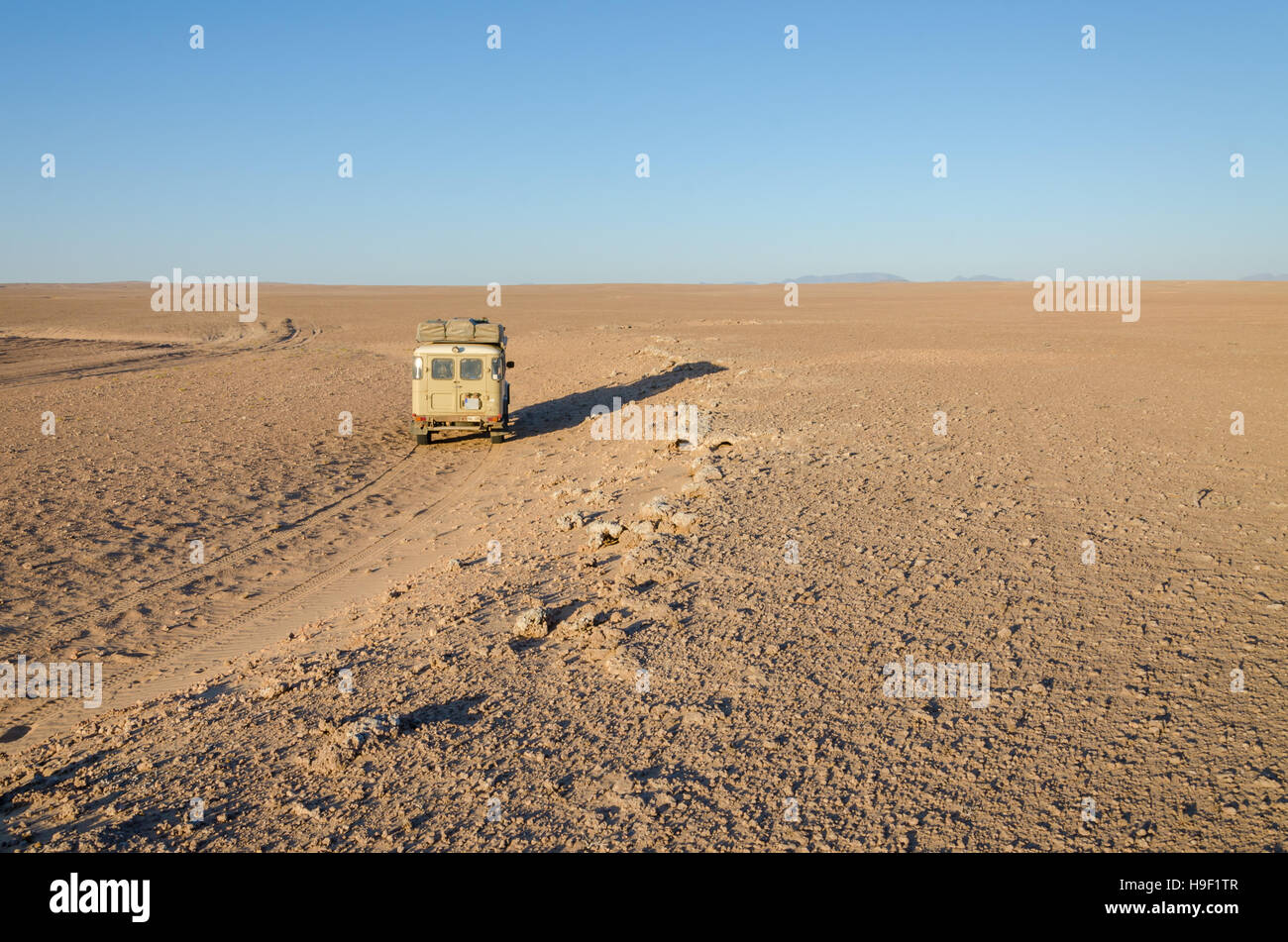4x4 offroad vehicle driving in empty flat and rocky Namib Desert of Angola. - Stock Image