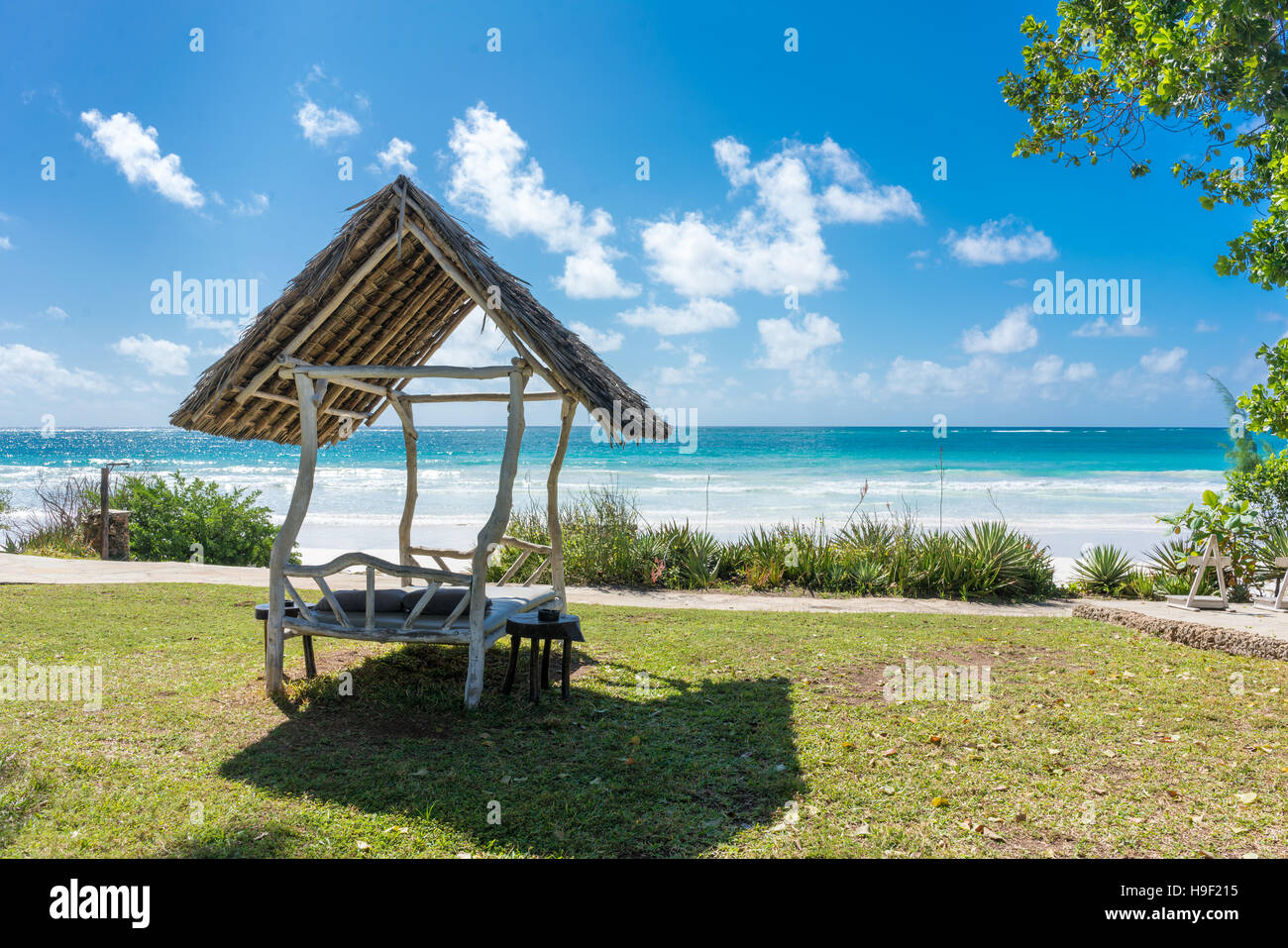 A shaded resting place with a thatched roof along Diani Beach - Stock Image