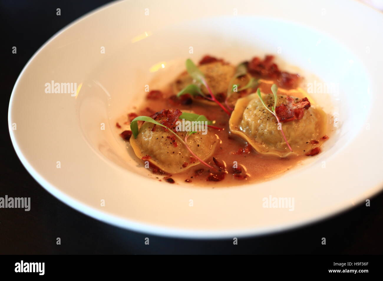 Cabbage ravioli with crispy bacon and pepper sauce - Stock Image