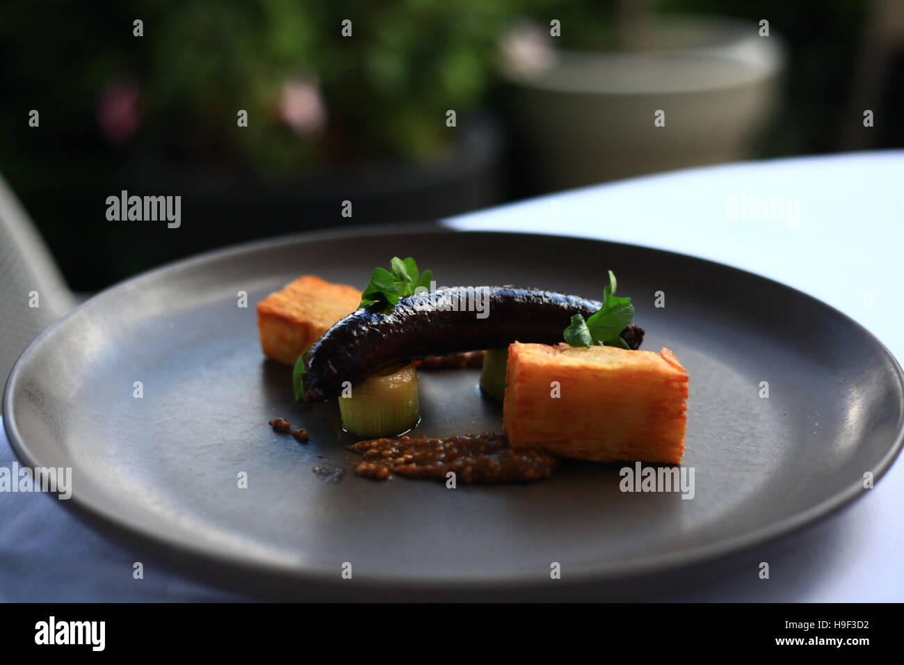 Black pudding sausage with mille feuille potato, caramelized leek and grainy mustard - Stock Image