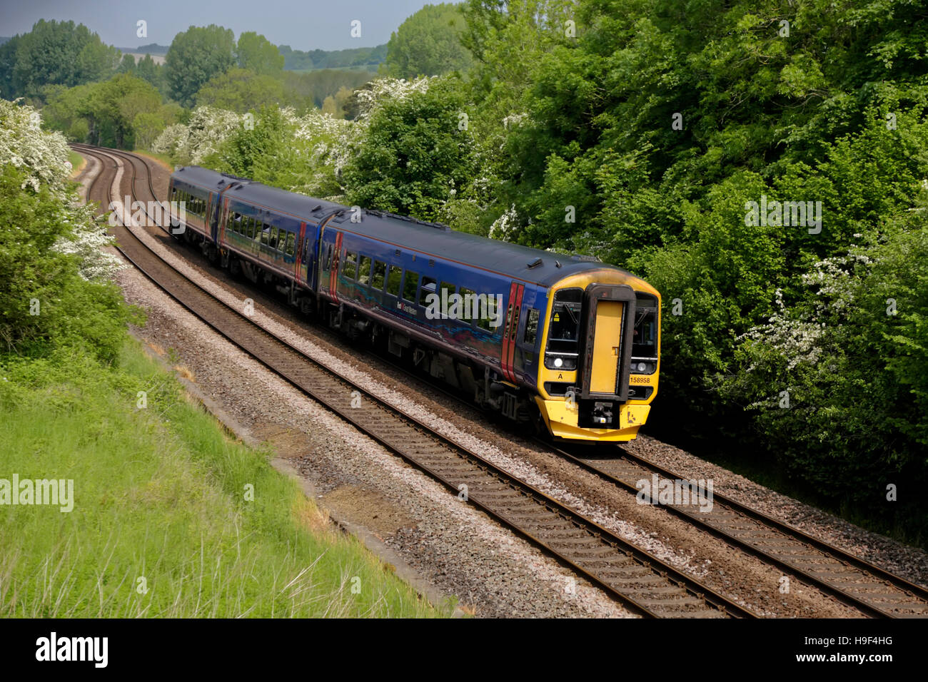 A British Rail Class 158 Express Sprinter train in First Great Western Livery passes Sherrington village in Wiltshire, - Stock Image