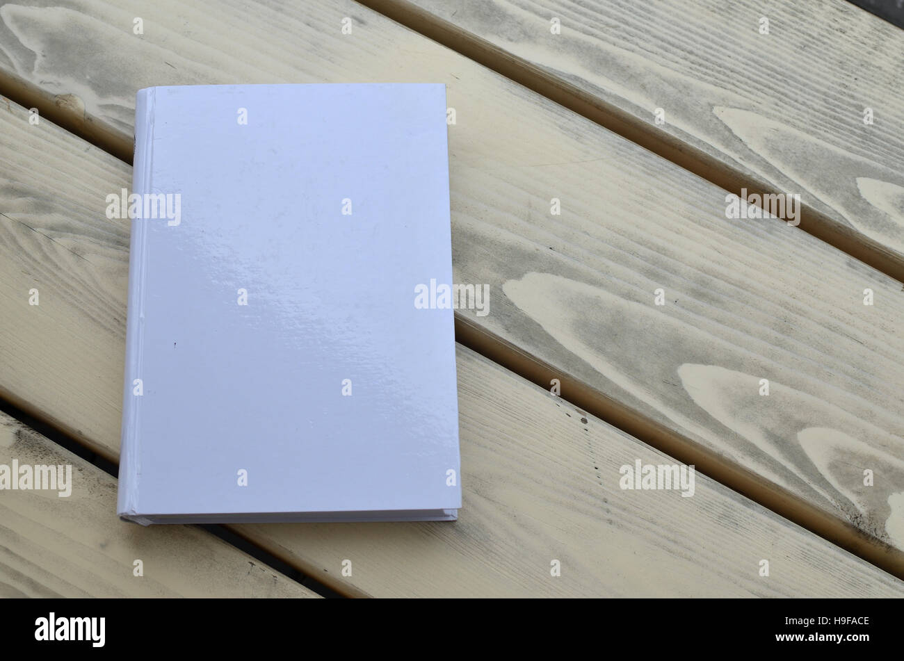 White hard cover book on a wooden bench - Stock Image