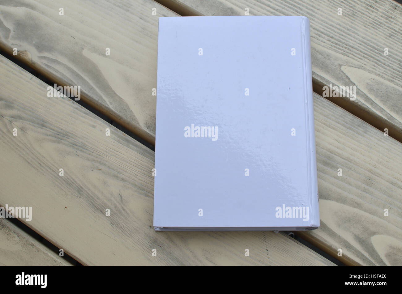 Closed white hard cover closed book on a wooden bench - Stock Image