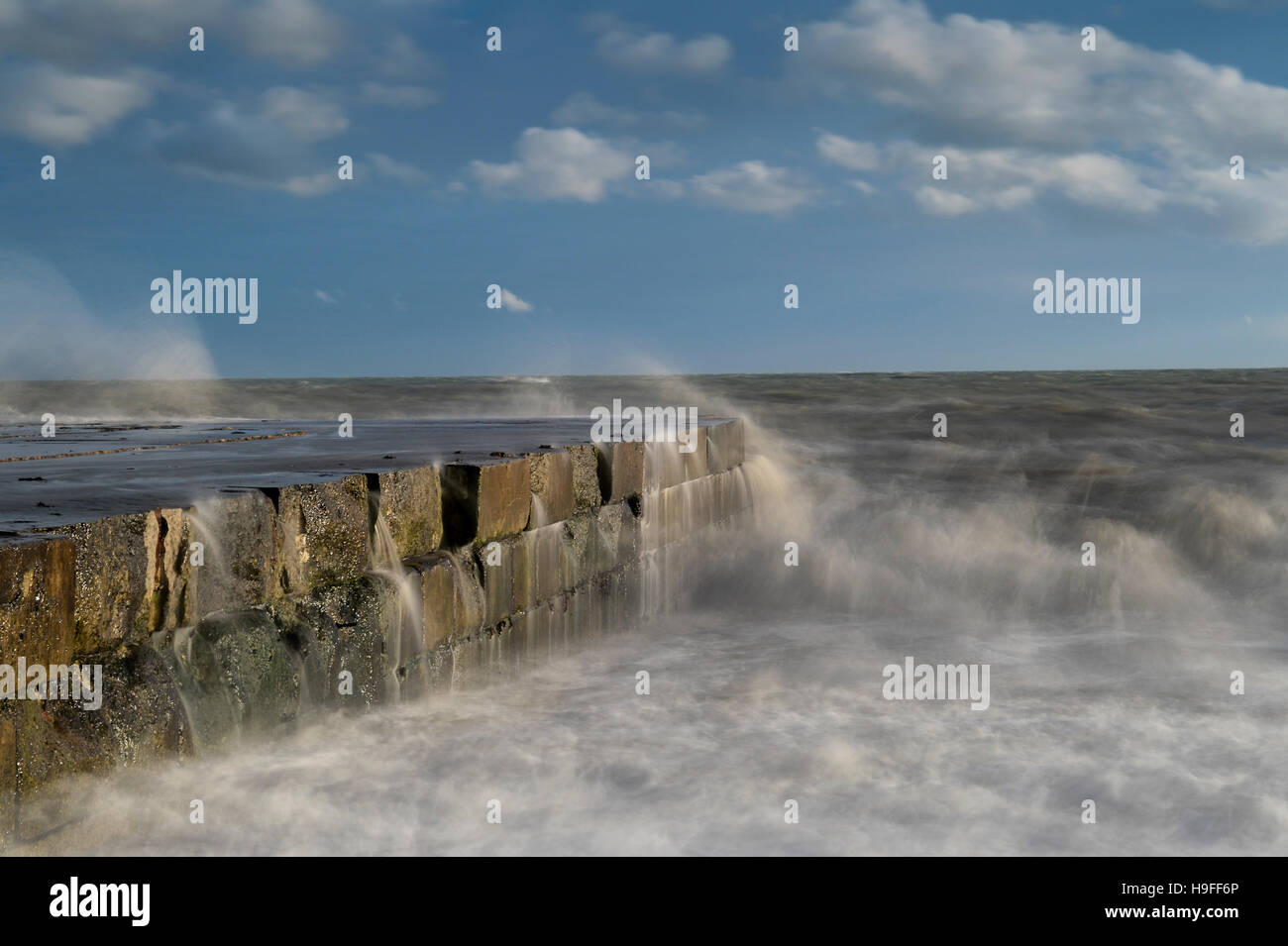 Tide breaks over the apron at Folkestone Warren, Kent. - Stock Image