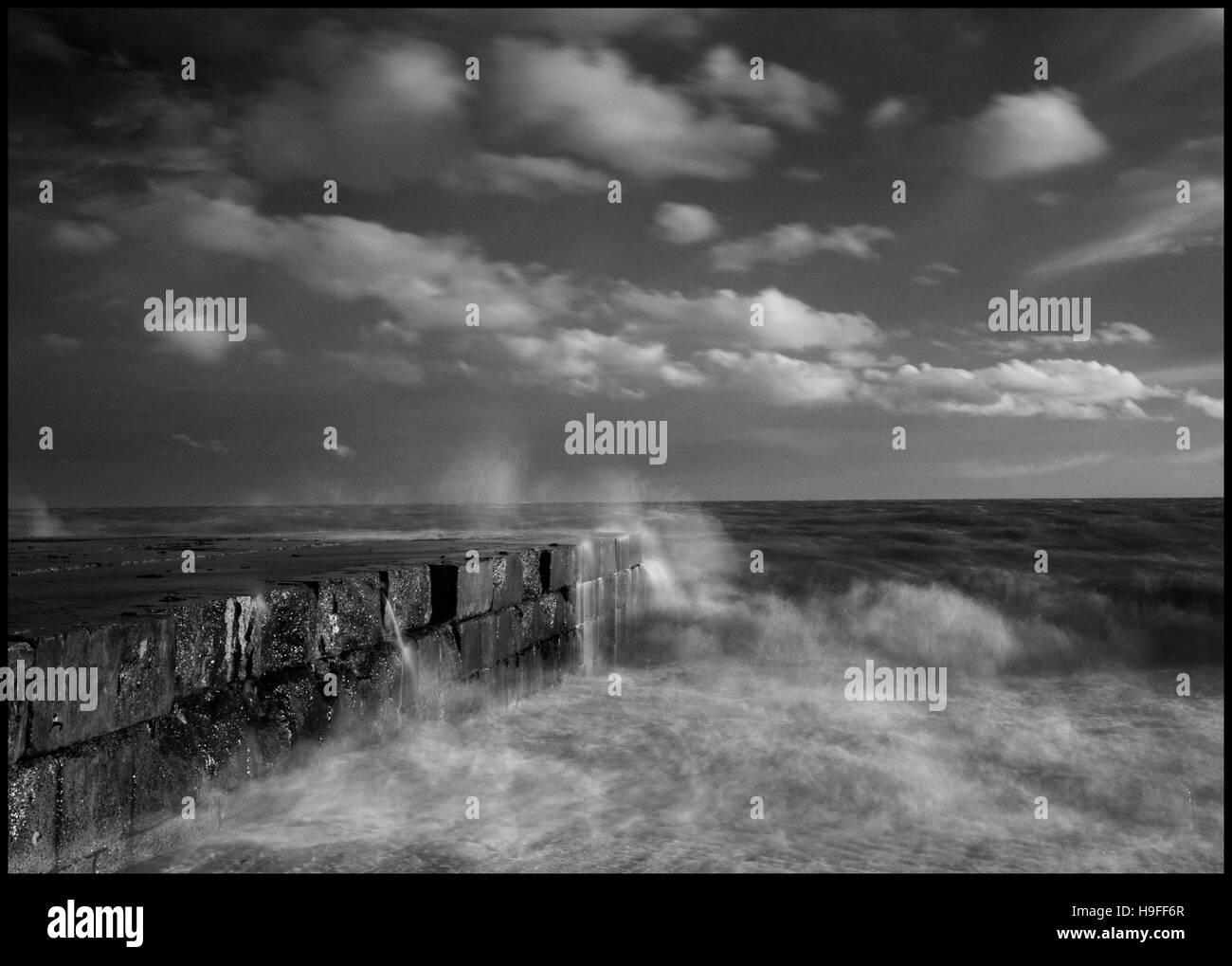Waves break over the apron at Folkestone Warren, Kent. - Stock Image