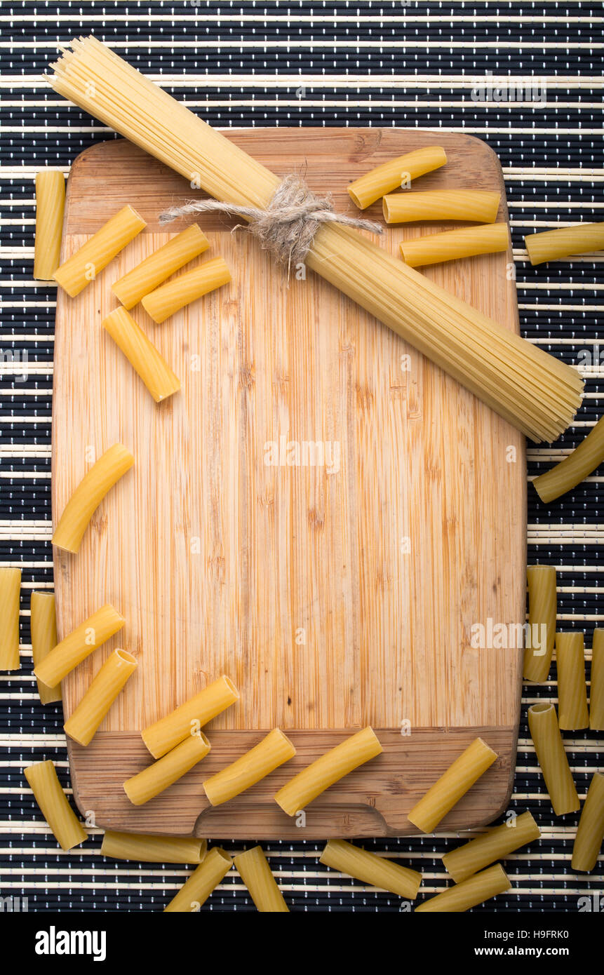 Food background with ingredients on the table, wooden base, a bunch of thin spaghetti and pasta on a striped background - Stock Image
