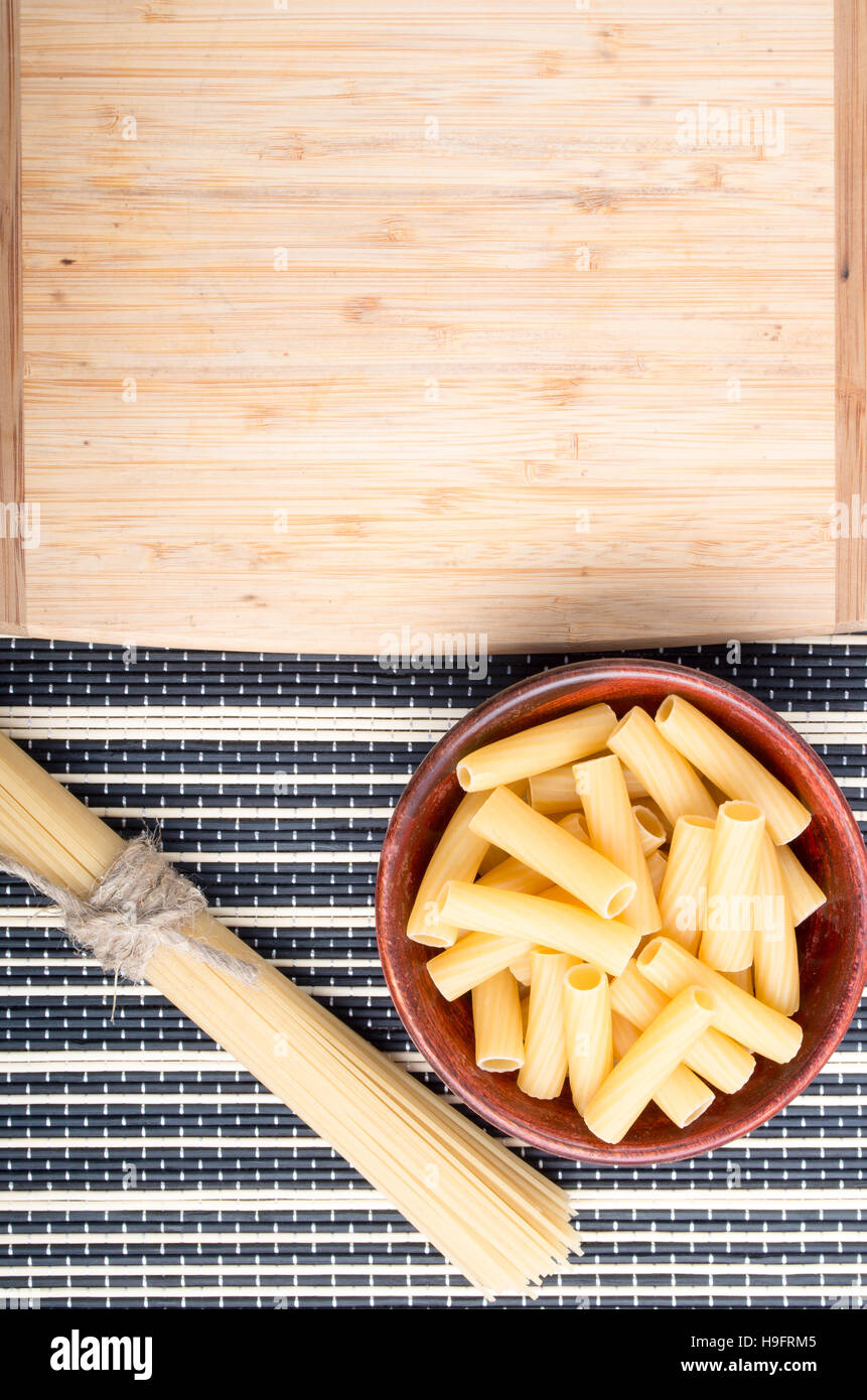 Top view of pasta in a wooden bowl with a bunch of spaghetti next to a wooden plank for cooking on a striped background Stock Photo