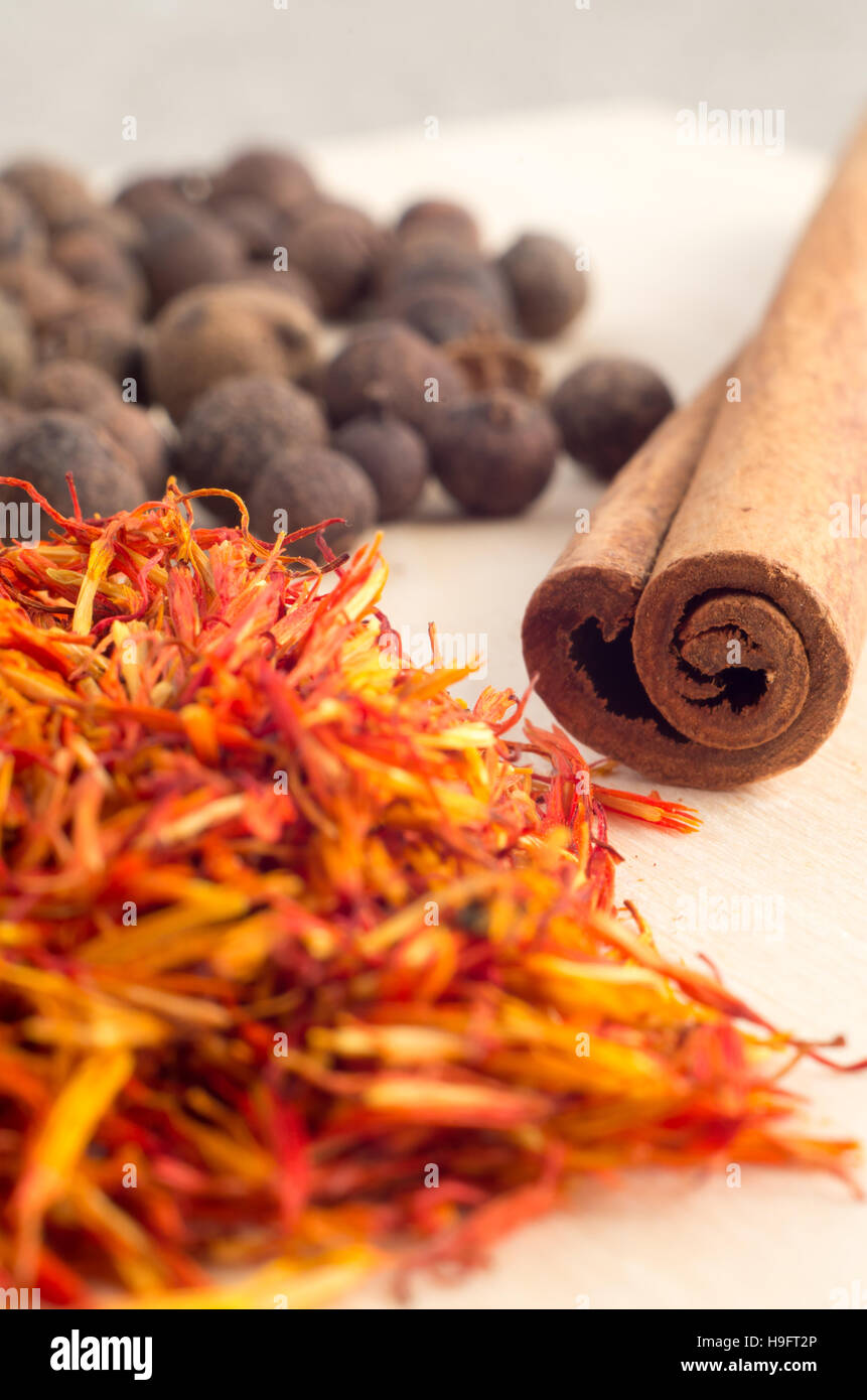 Condiments and spices - cinnamon sticks, allspice and fragrant saffron close-up with shallow depth of focus. - Stock Image