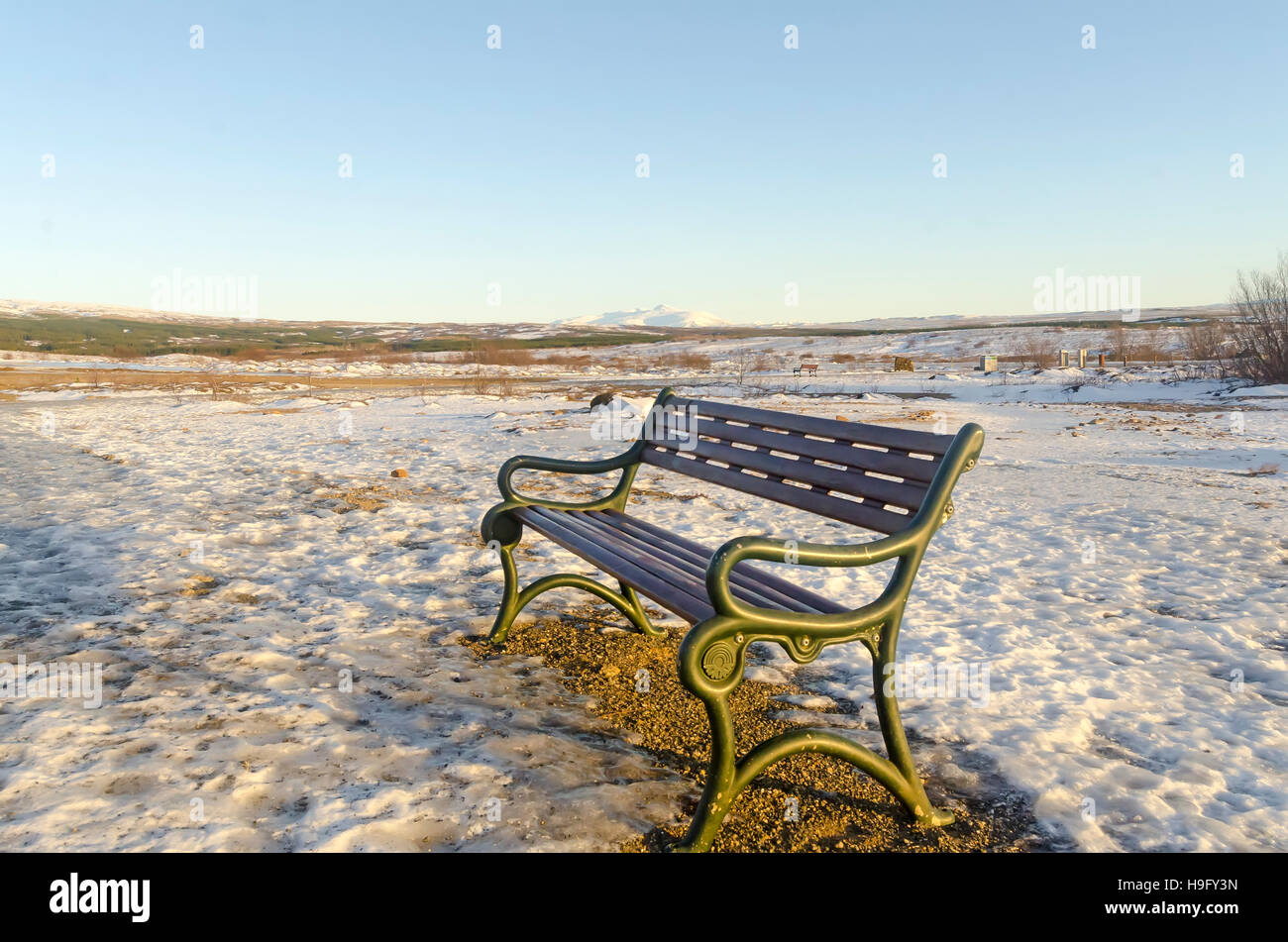 Empty Metal Bench winter deserted wilderness landscape on clear day. - Stock Image