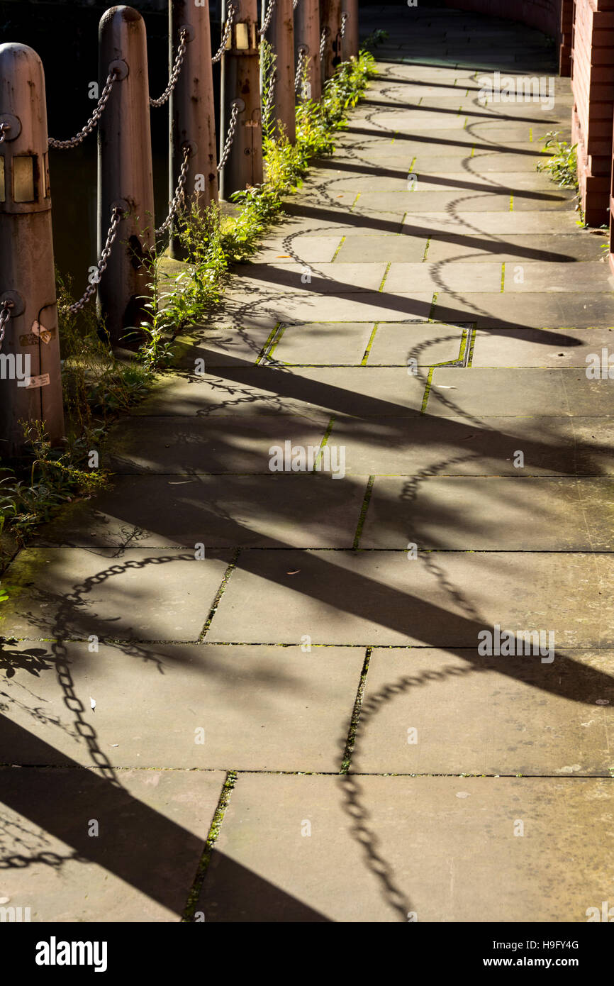 Shadow of the chain fence on the former Manchester and Salford Junction Canal, alongside the Bridgewater Hall , - Stock Image